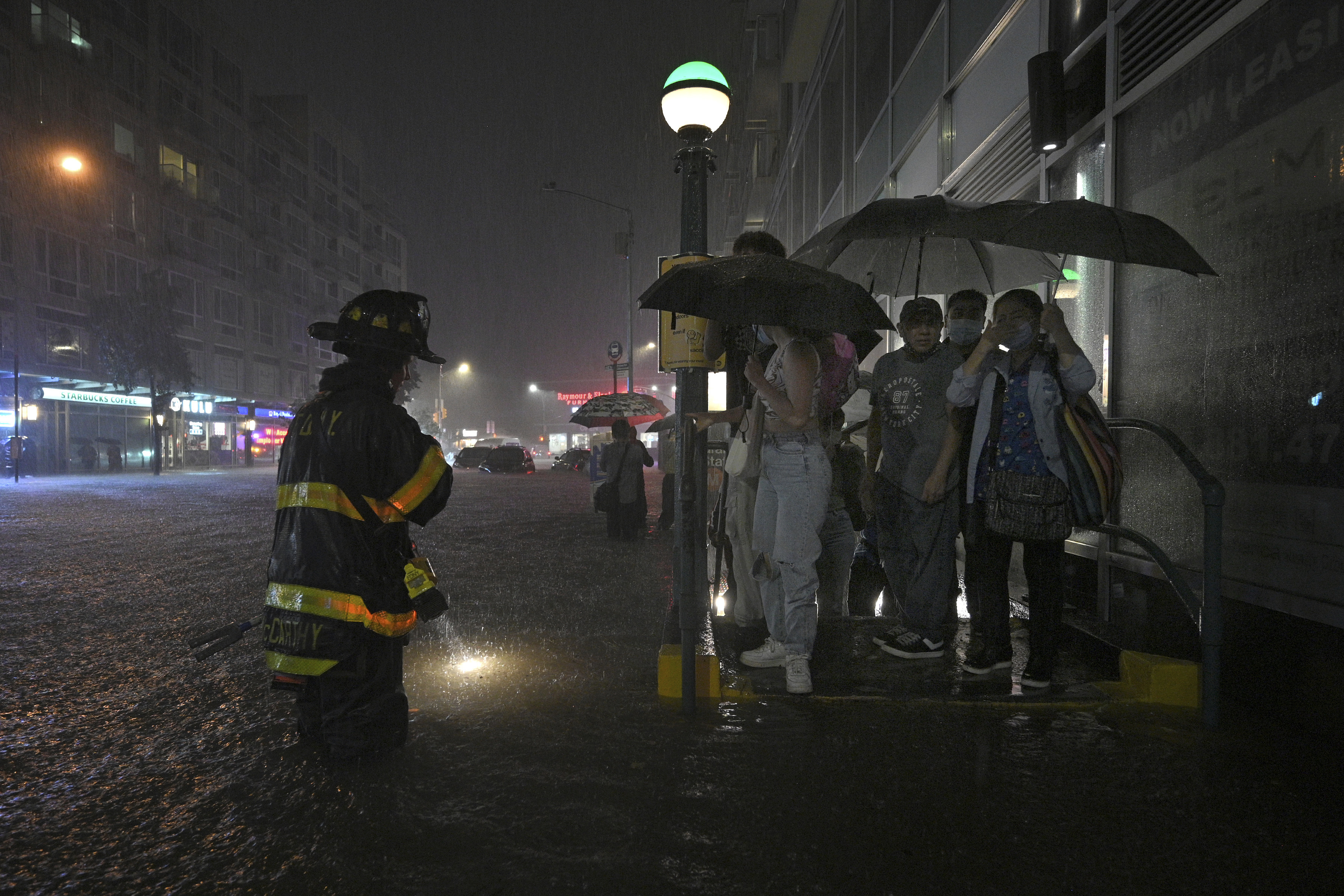 A firefighter directs people stranded at a subway entrance during flash flooding in New York on September 1.