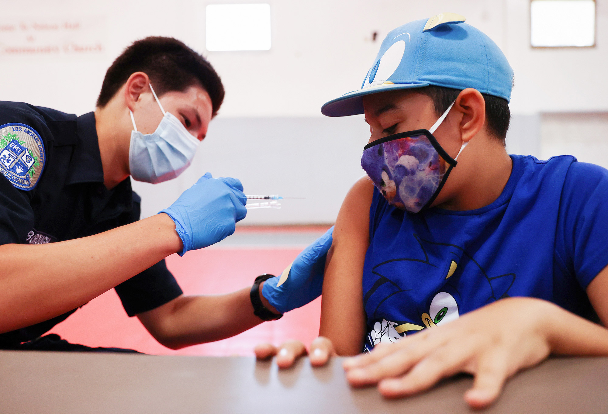 EMT Quentin Scarborough administers a vaccine dose to Nathan Alex Perez during a pop-up COVID-19 vaccination clinic at James Jordan Middle School on July 6 in Winnetka, California.