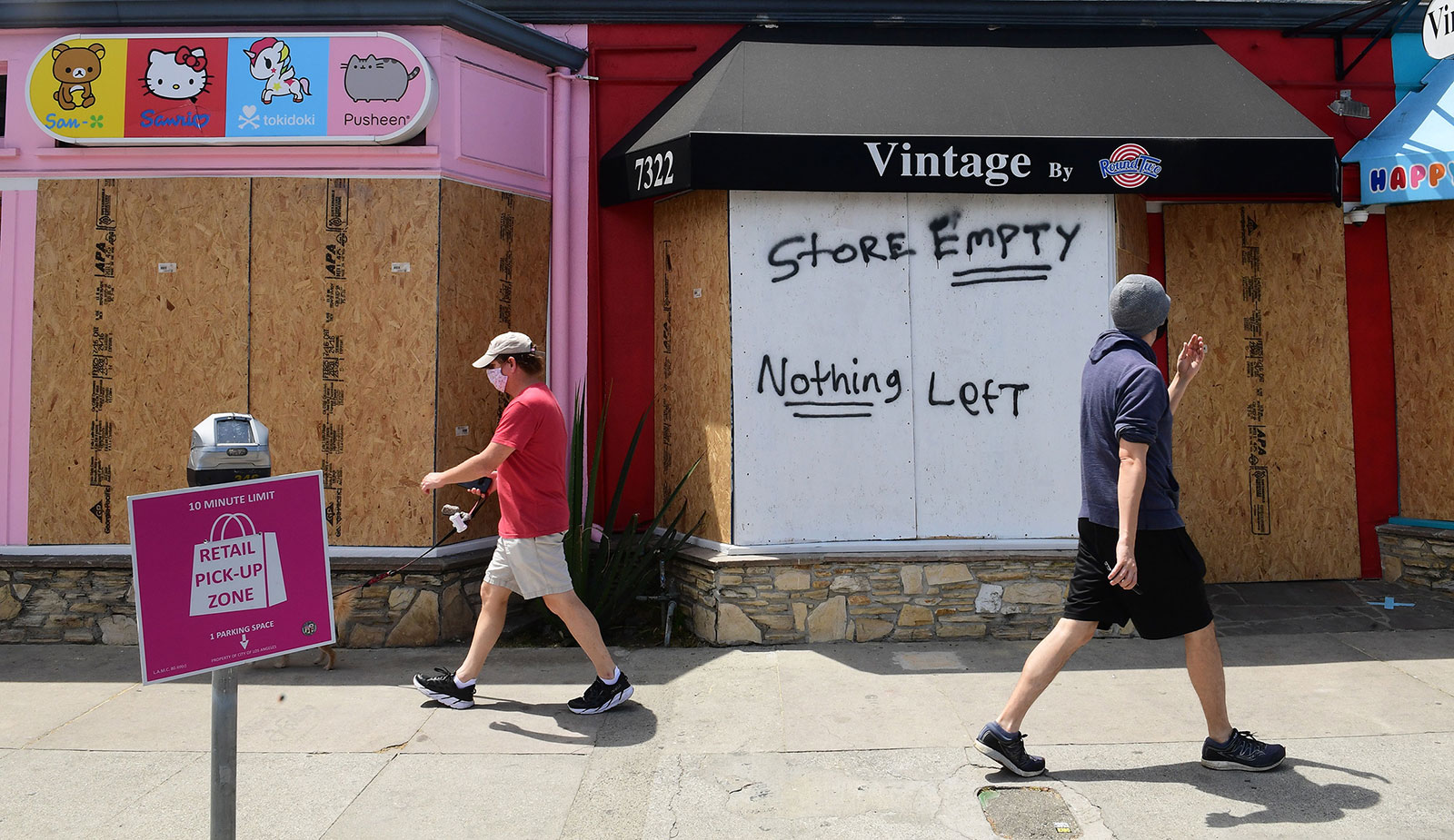 Pedestrians walk past boarded up storefronts on Melrose Avenue in Los Angeles on June 1.