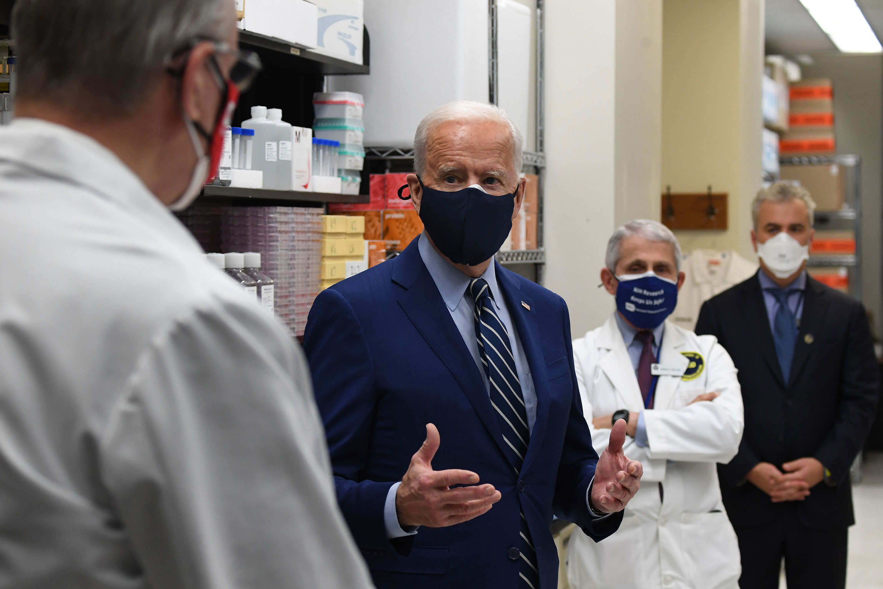 President Joe Biden speaks to Dr. Barney S. Graham, left), as Dr. Anthony Fauci listens during a tour of the Viral Pathogenesis Laboratory at the National Institutes of Health in Bethesda, Maryland, on February 11.