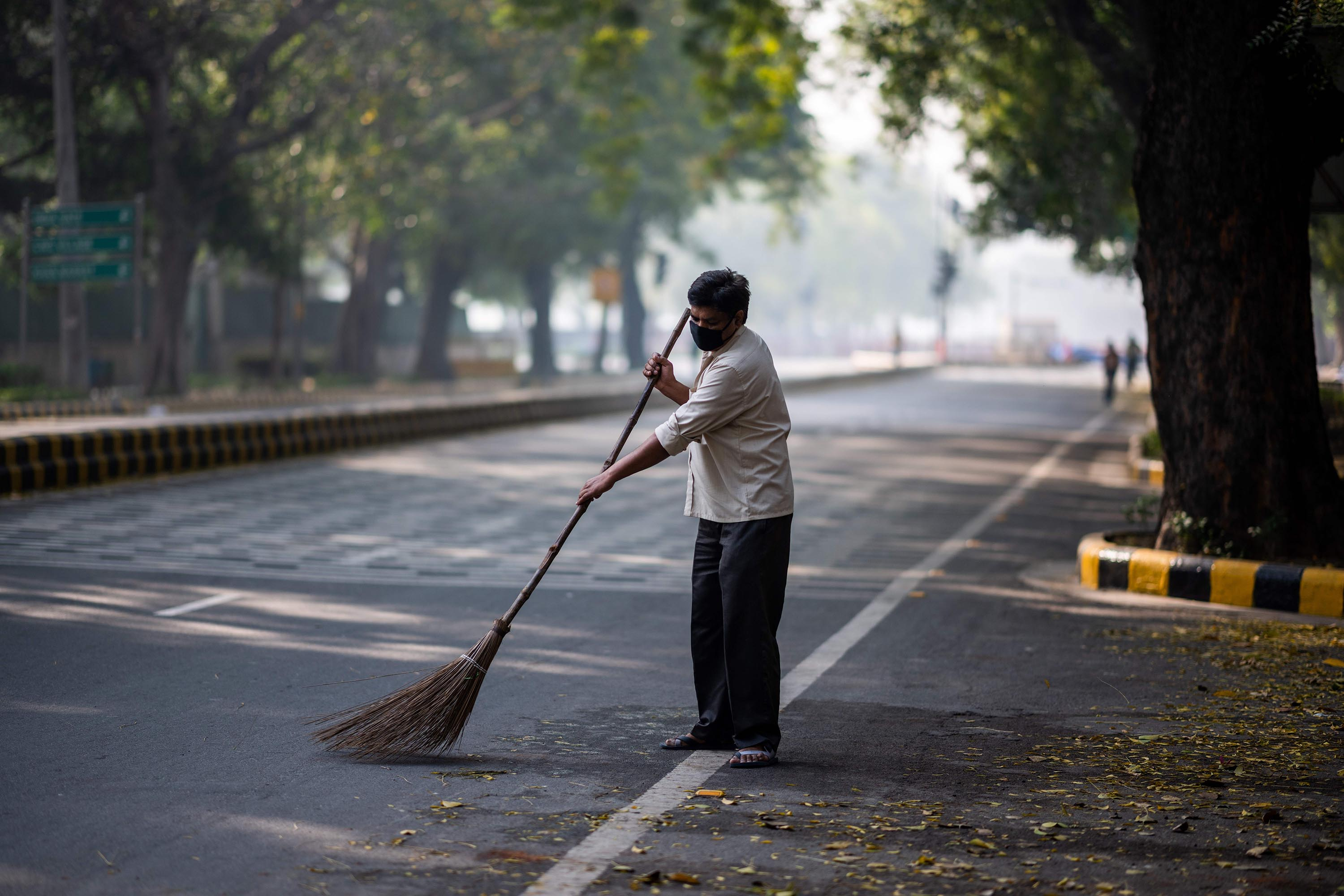 A man sweeps a street in New Delhi on March 20.