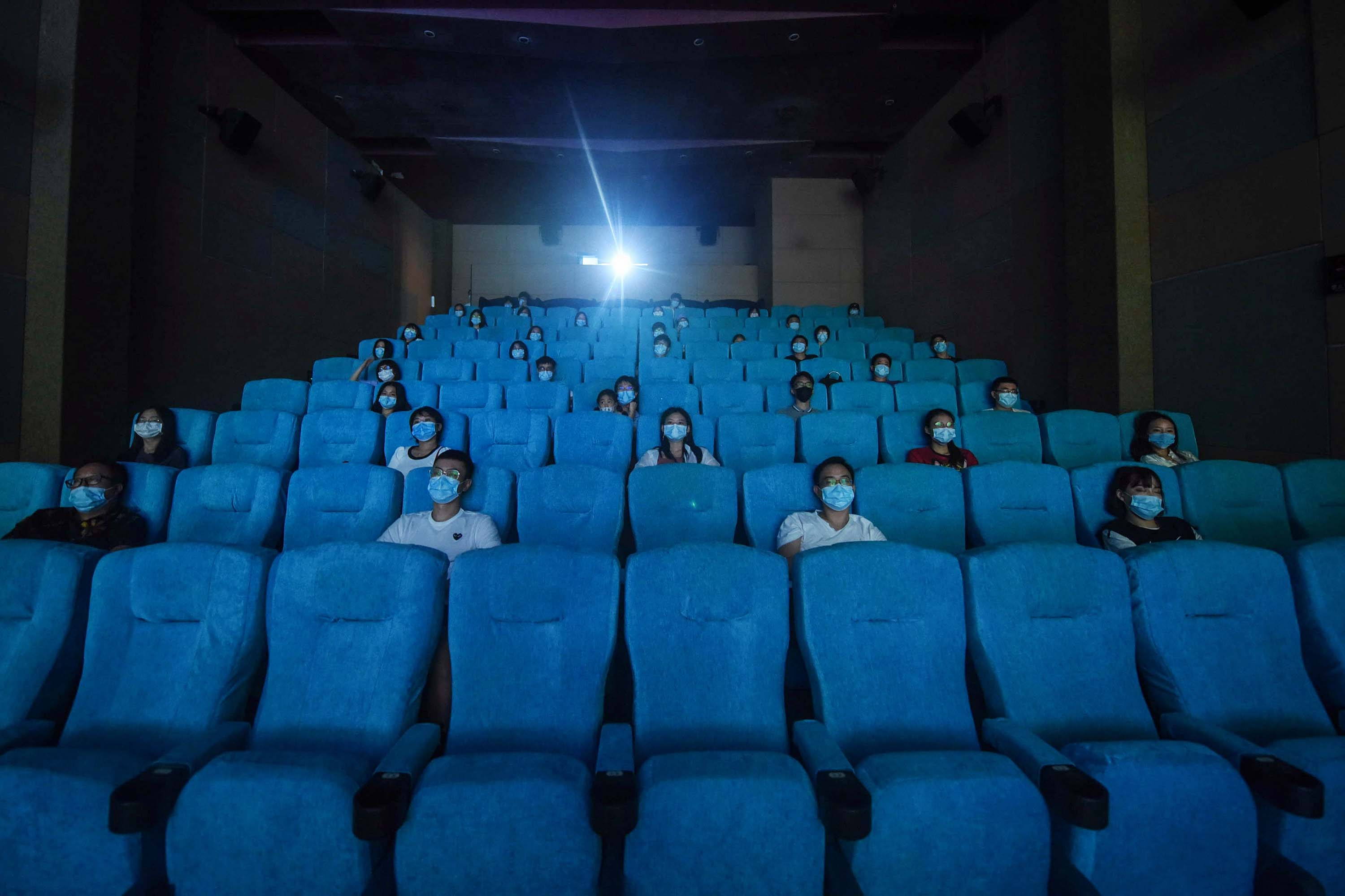 People watch a movie as they sit socially-distanced at a cinema in Hangzhou, China, on July 20.