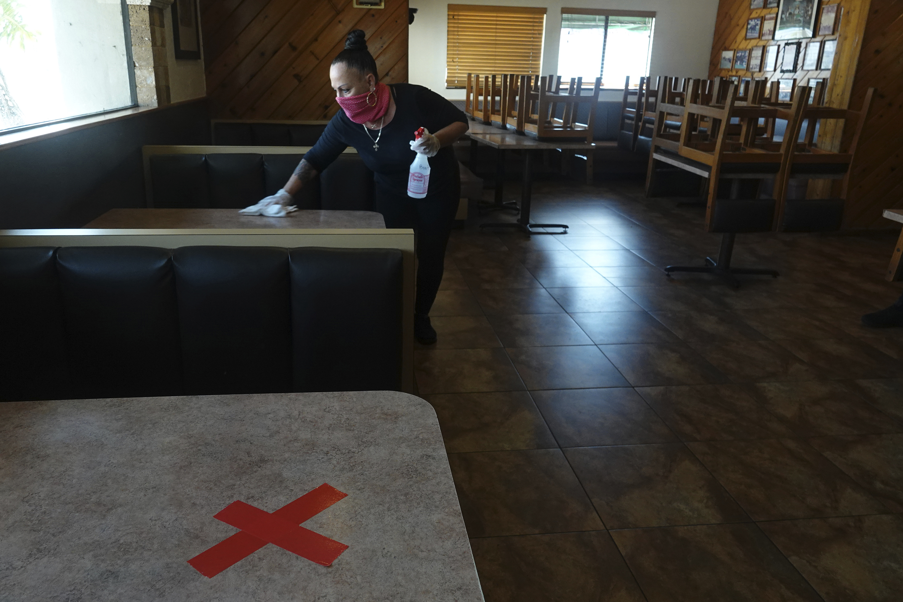 Head waitress Barbara Rogers disinfects tables at the Peter Pan Diner in Oakland Park, Florida, on May 17. Broward County businesses are set to partially reopen on May 18.
