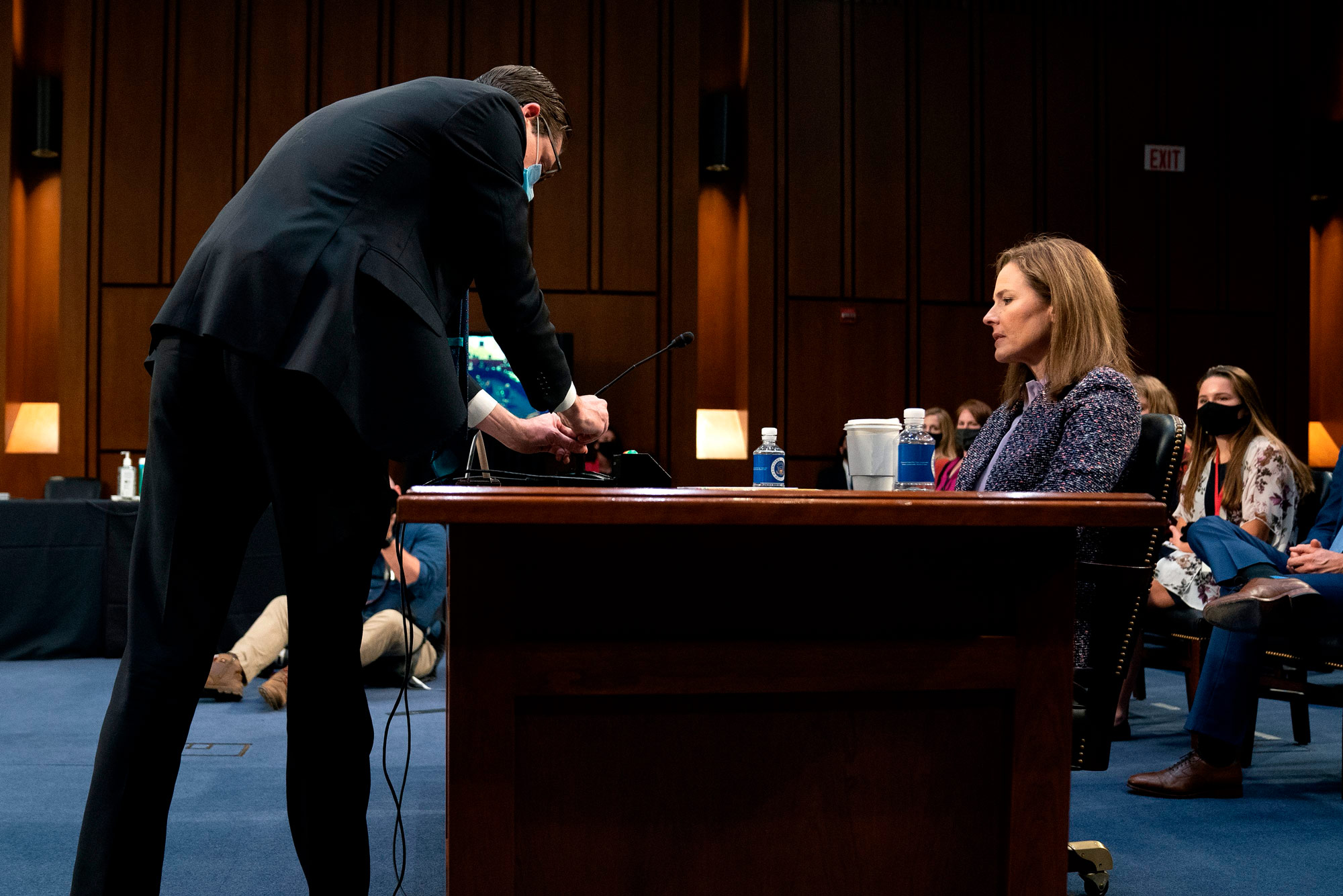 A staff member, left, attempts to fix the microphone for Judge Amy Coney Barrett during a Senate Judiciary Committee confirmation hearing in Washington, DC, on October 14.