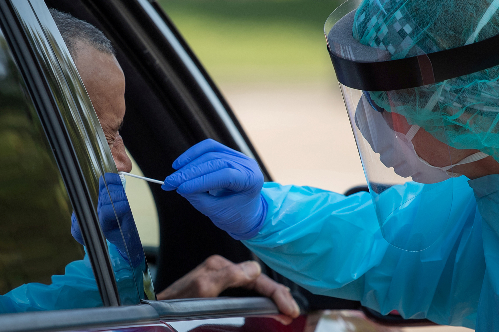 A healthcare worker uses a swab to test a man at a Covid-19 drive-in testing location in Houston, Texas.
