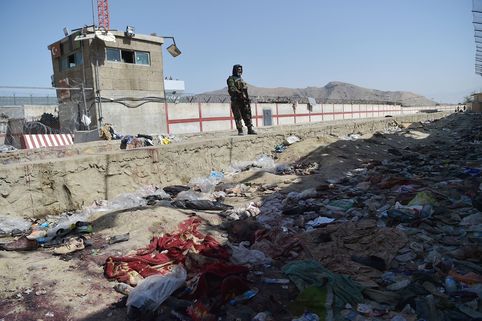 A Taliban fighter stands guard at the site of the August 26 suicide bombs on August 27.