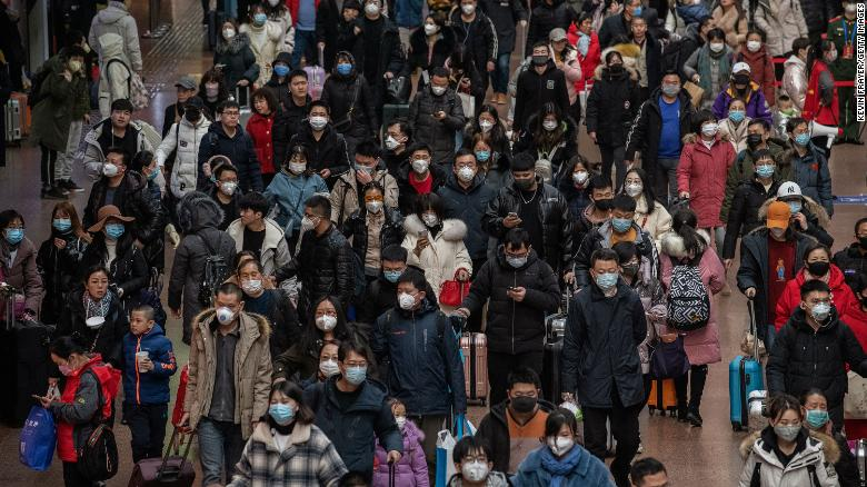 Chinese passengers, most wearing masks, arrive to board trains before the Lunar New Year at a Beijing railway station.