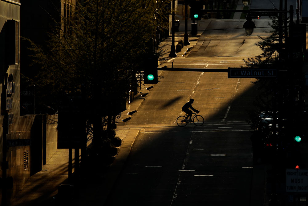 A man on a bicycle crosses an empty downtown street in Kansas City, Missouri on Wednesday, April 15, while stay-at-home orders continue in the state and much of the rest of the country as part of an effort to curb the spread of the new coronavirus.