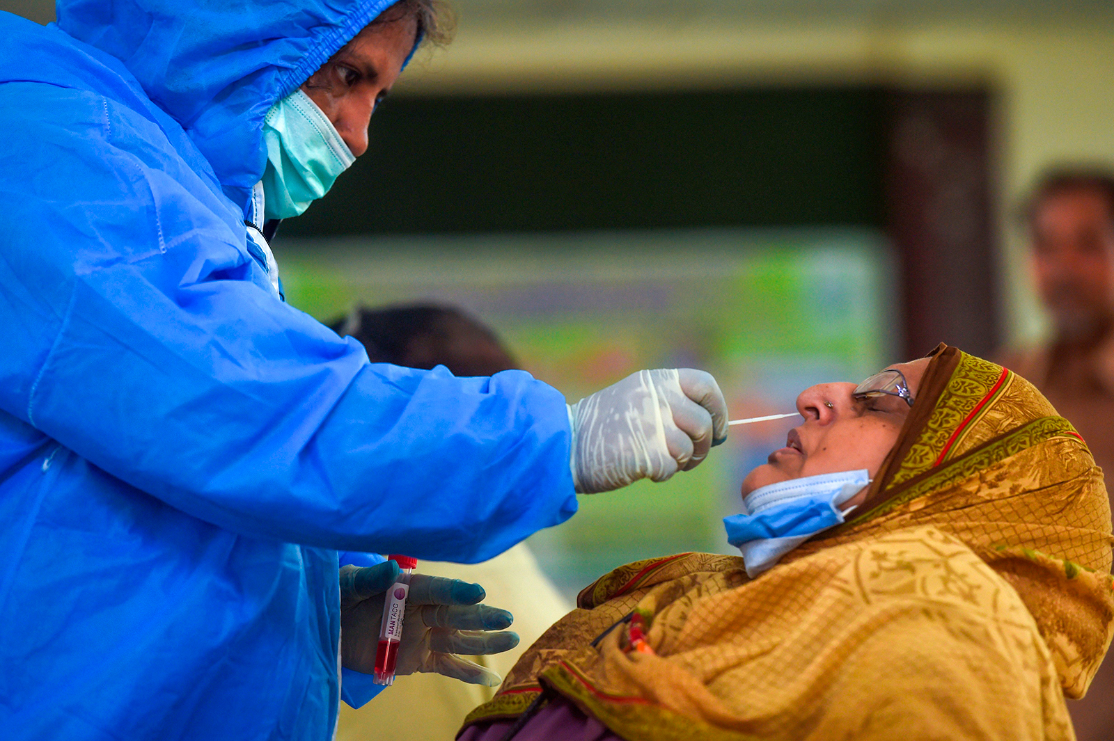 A health official collects a swab sample from a woman to test for Covid-19 in Karachi, Pakistan on September 14.