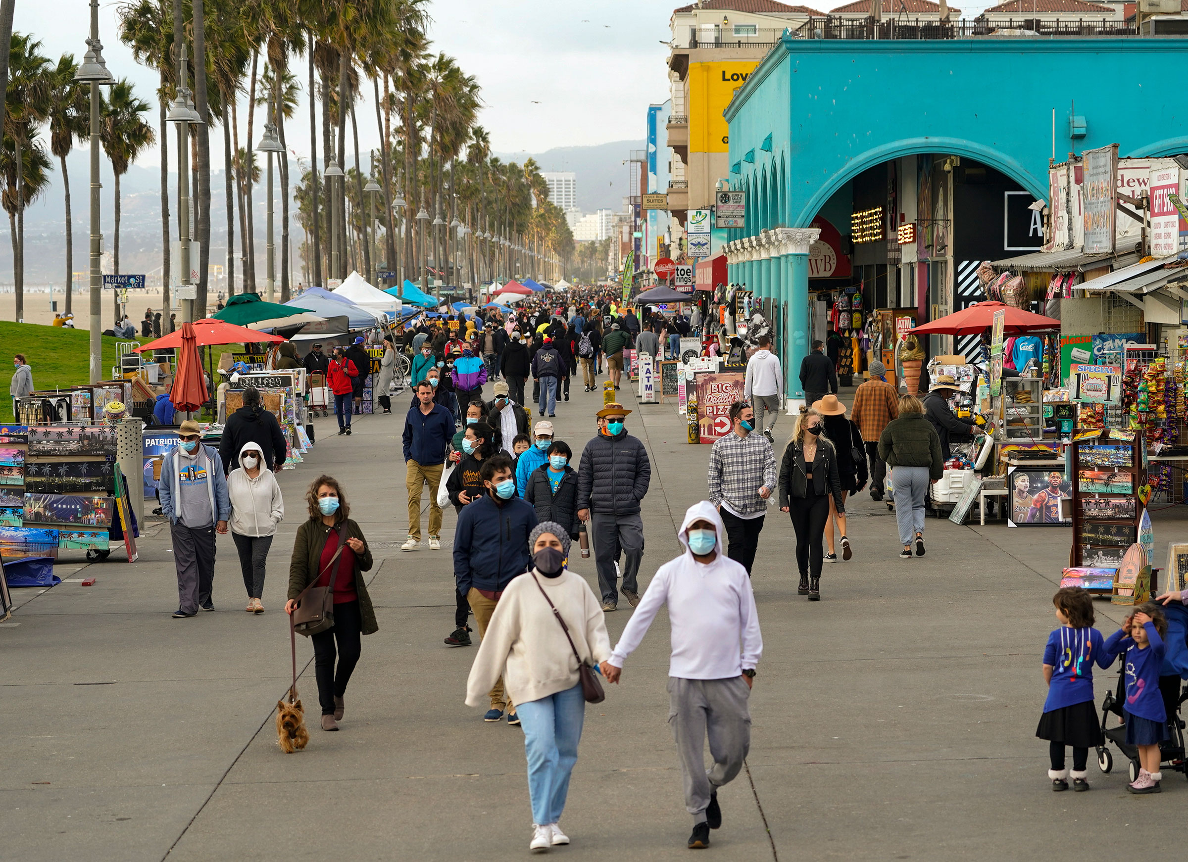 People walk along the Venice Beach Boardwalk on December 27 in Los Angeles, California.