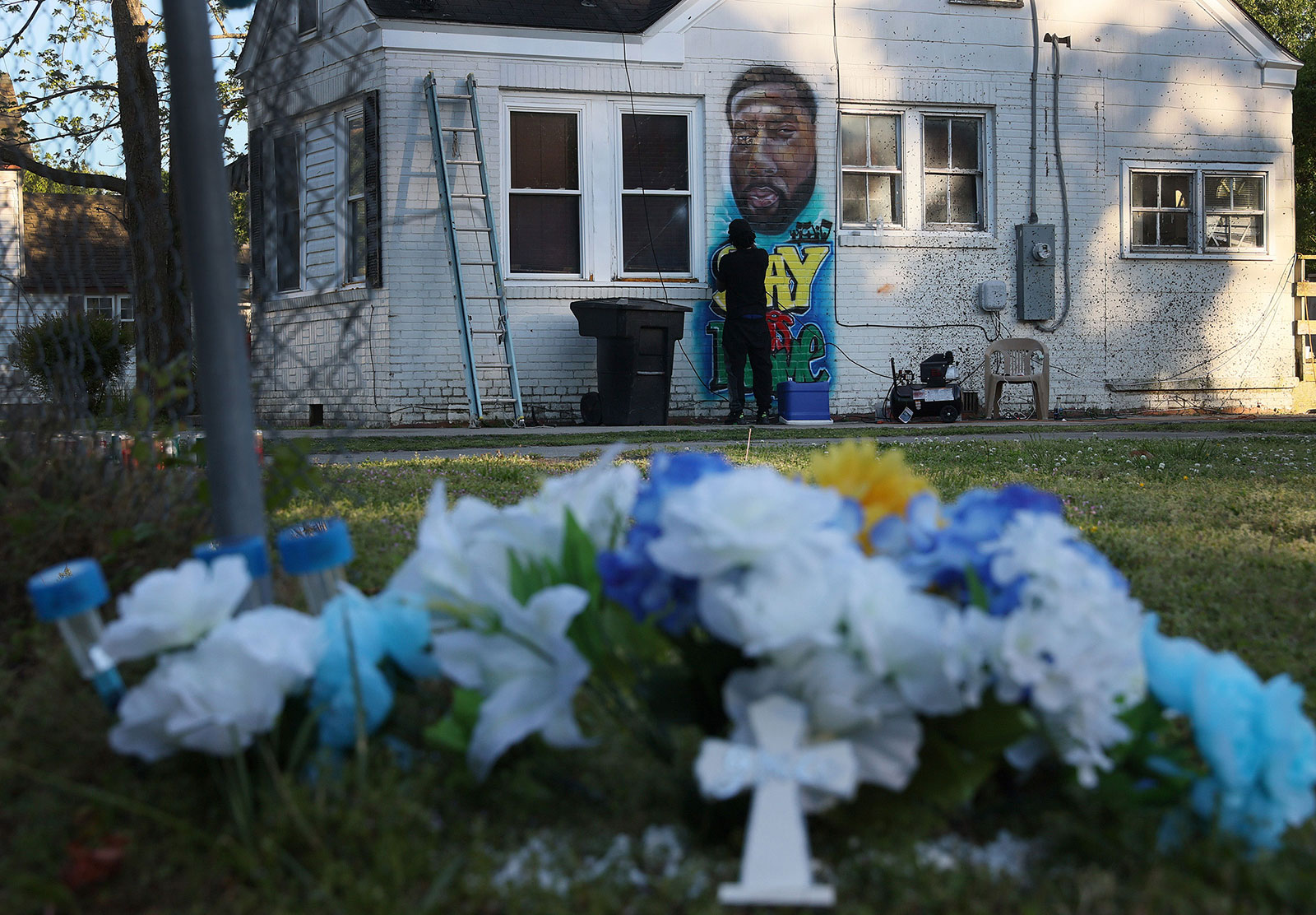 Ulysses Edwards paints a portrait of Andrew Brown Jr. on the side of a house near where he was killed in Elizabeth City, North Carolina.