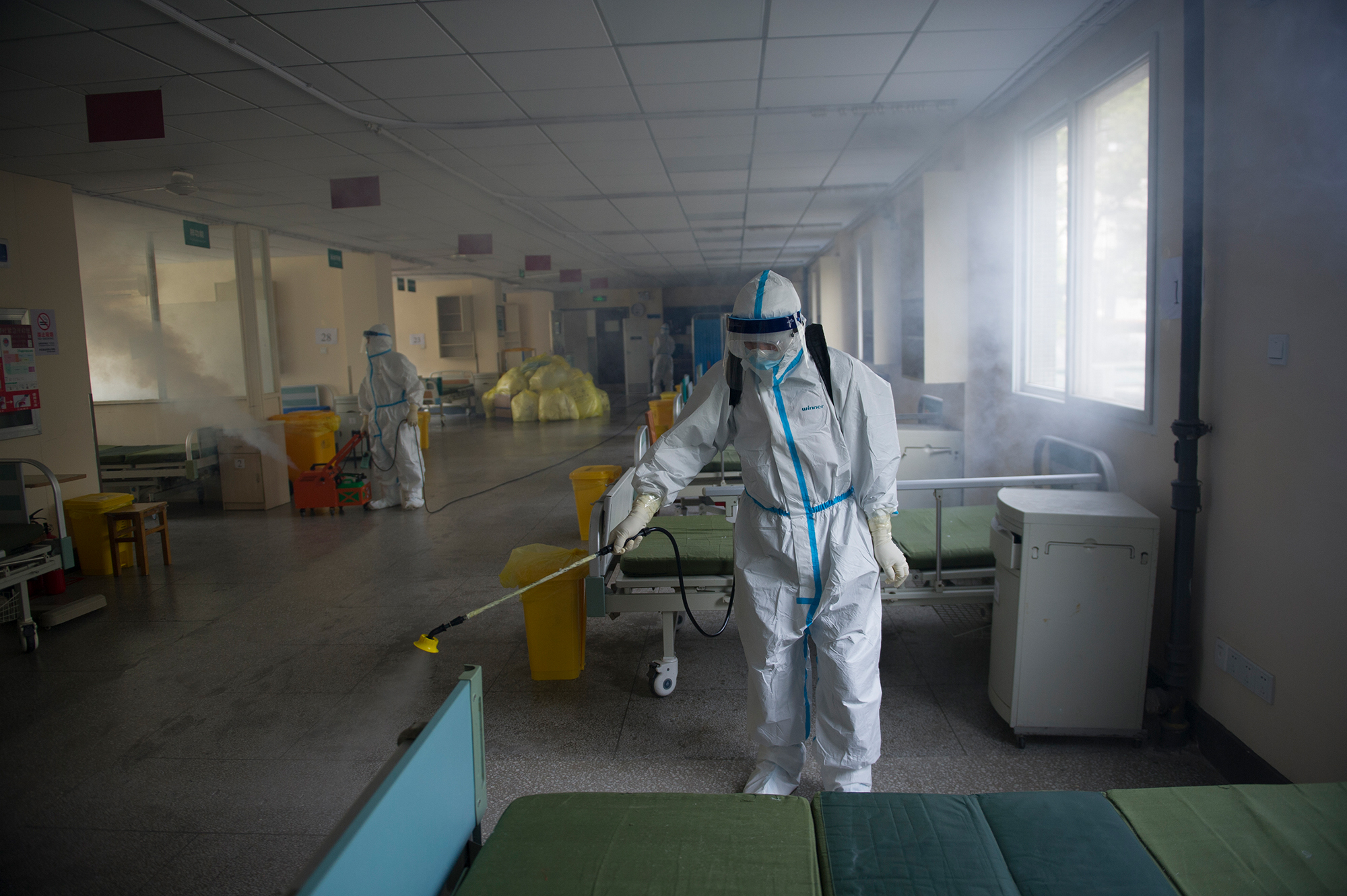 A worker disinfects around the No. 7 Hospital, once designated for only coronavirus patients, in Wuhan in central China's Hubei province on Thursday, March 19. The hospital is getting back to be a normal hospital after the last coronavirus patient was transferred away.