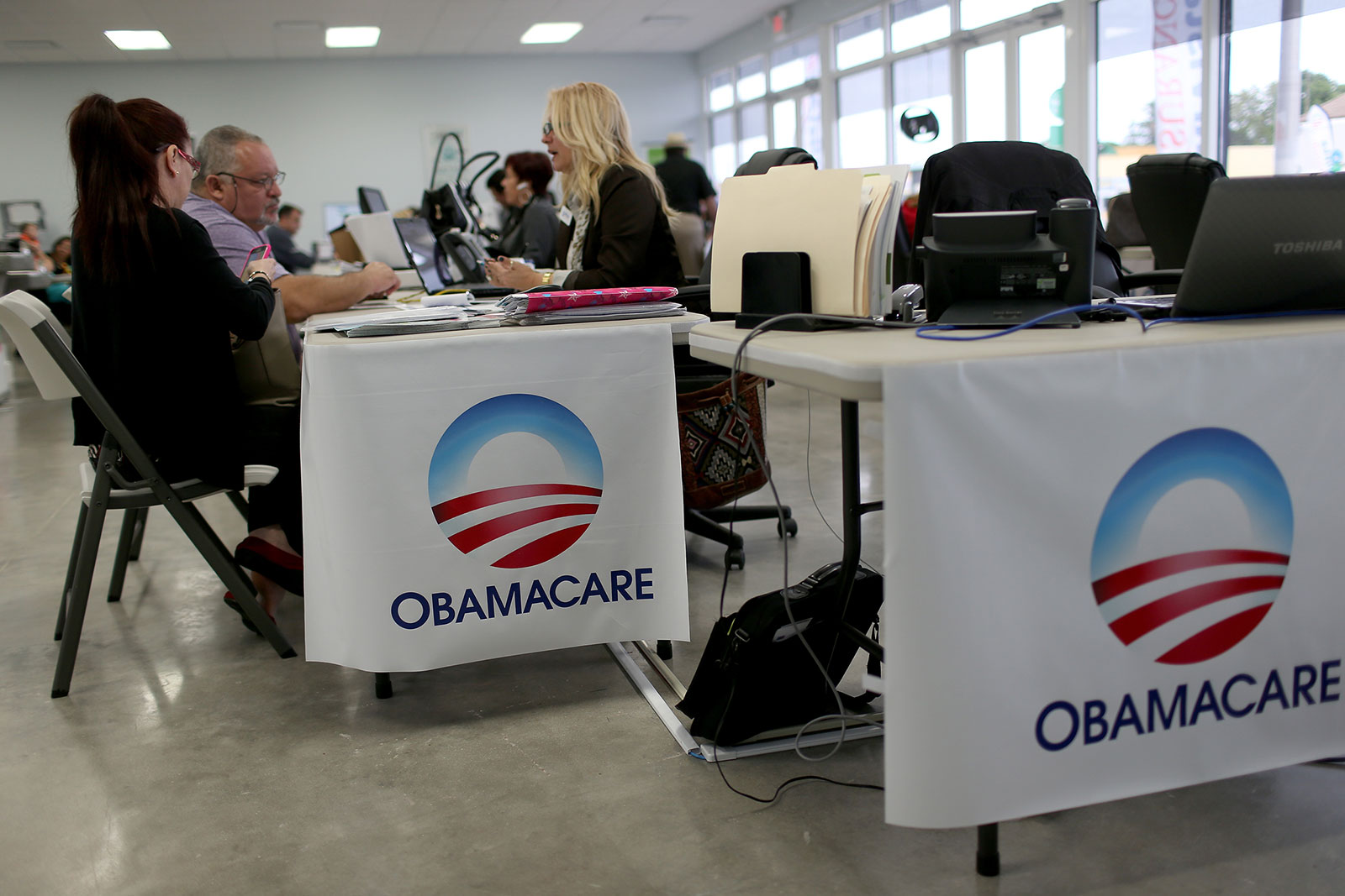 People sit down with an insurance adviser to sign up for health insurance through the Affordable Care Act in Miami, Florida, in 2015.