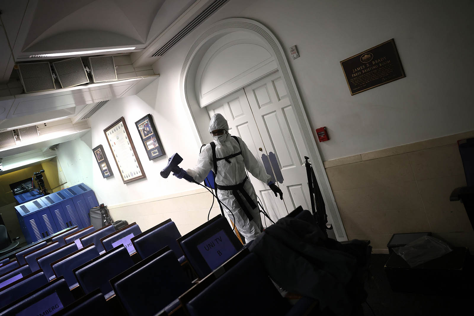 A member of the White House cleaning staff sanitizes the James S. Brady Press Briefing Room on October 5, in Washington.