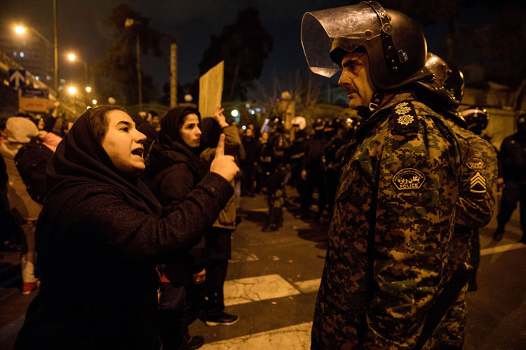 A woman at a candlelight vigil talks to a policeman following a gathering in front of the Amir Kabir University in Tehran on January 11.