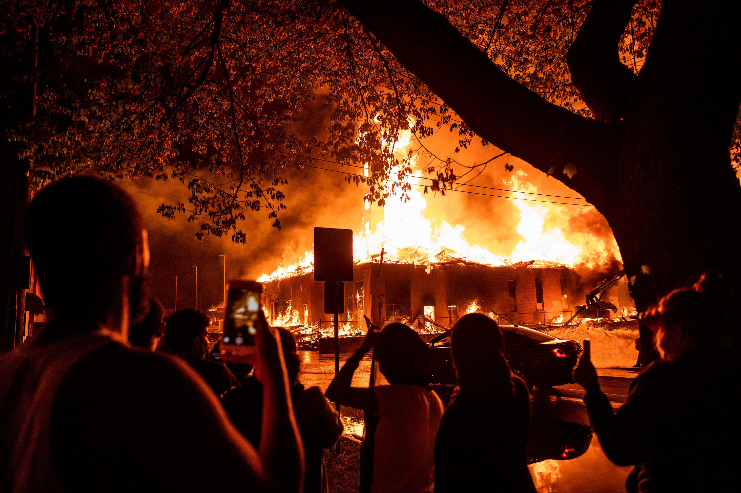 People look on as a construction site burns near the Third Police Precinct in Minneapolis, Minnesota, on May 27.