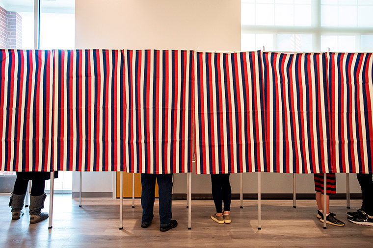 Voters fill in their ballots at polling booths for the presidential election in Concord, New Hampshire, on November 3, 2020.