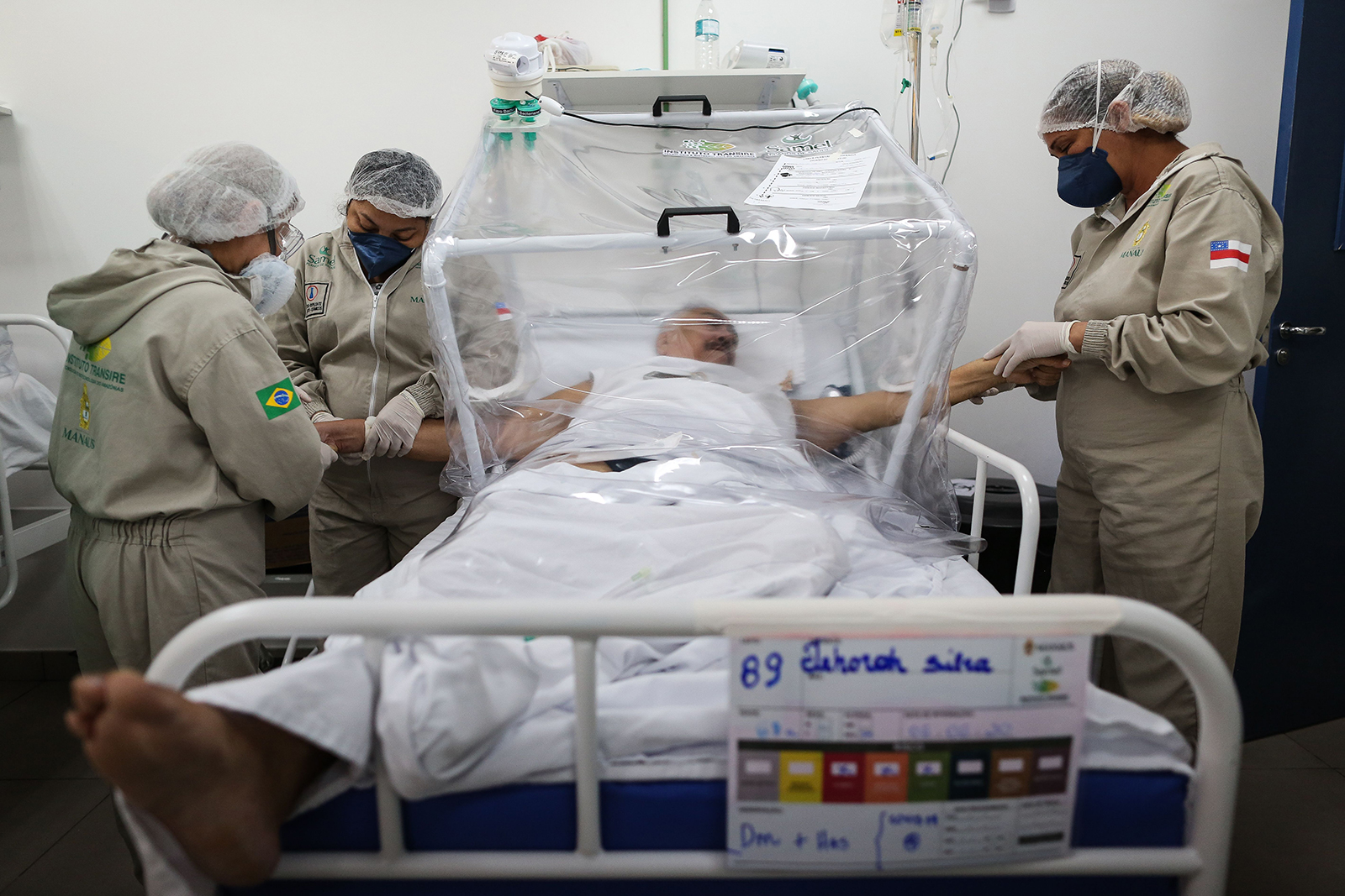 Health workers assist a COVID-19 patient at the Gilberto Novaes Municipal Hospital in Manaus, Brazil, on June 8.