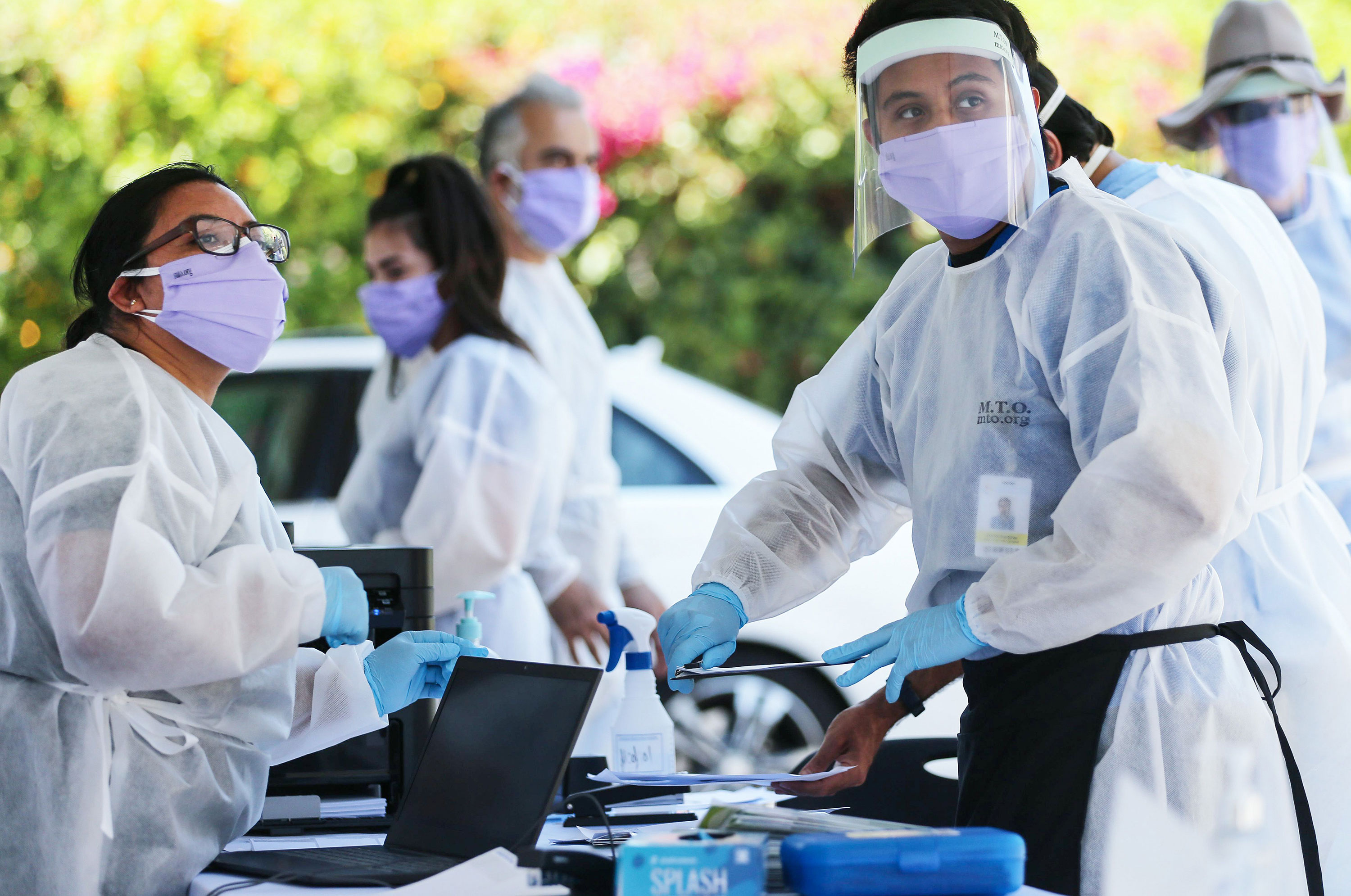 Healthcare workers facilitate tests at a drive-in coronavirus testing center on August 11 in Los Angeles, California.
