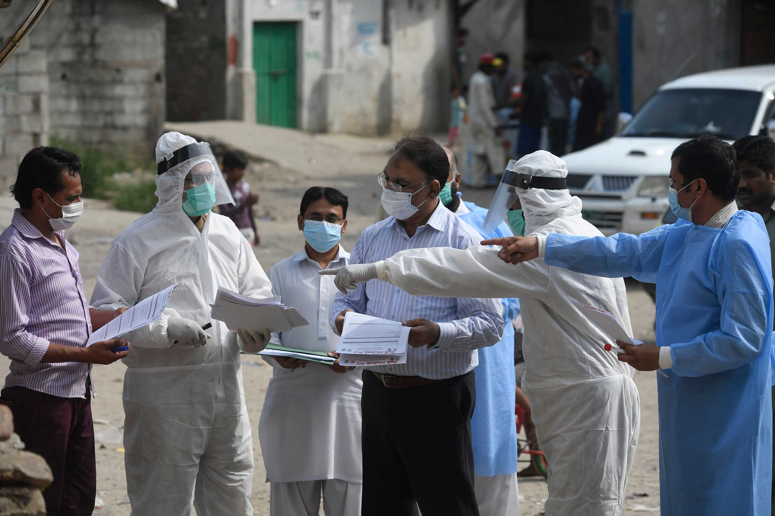 Health officials hold medical records after collecting samples from residents during a door-to-door screening and testing operation at a slum area in Islamabad, Pakistan, on June 30.