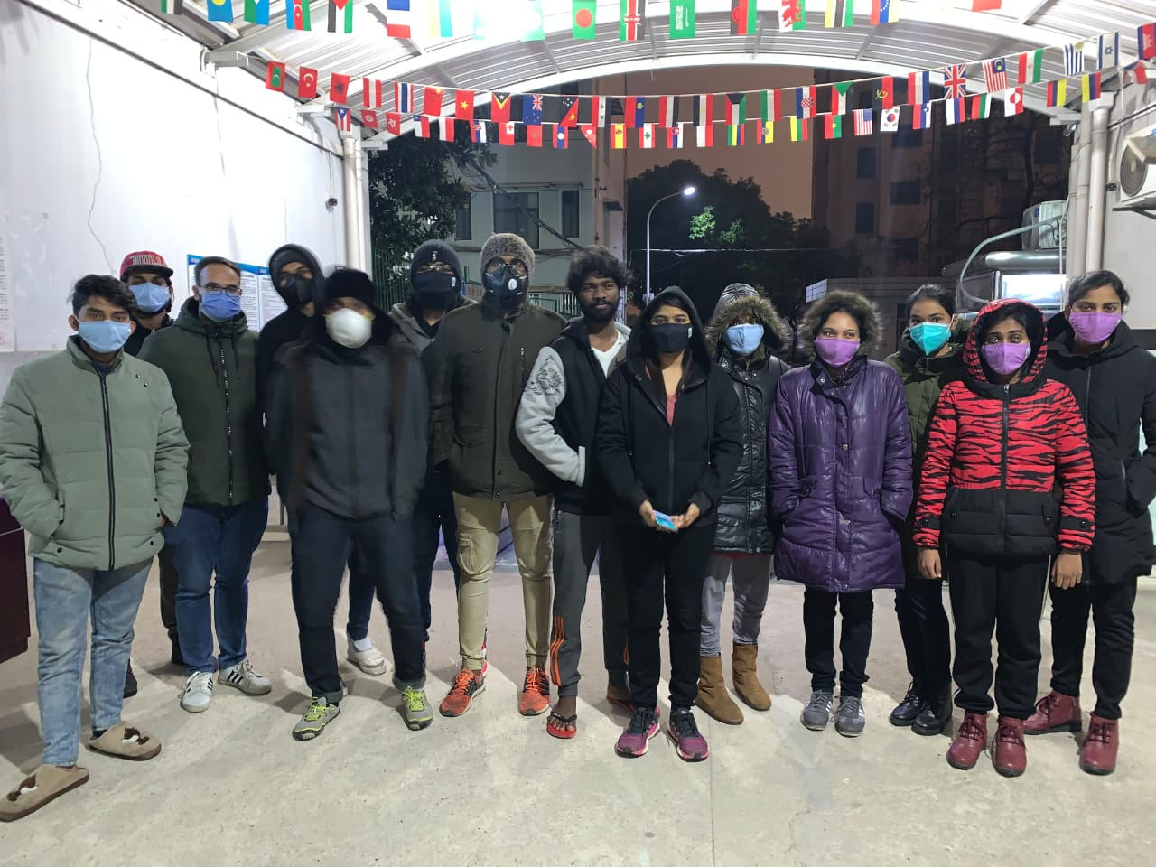 Indian students stand outside the foreign dormitory entrance at Wuhan Medical University.
