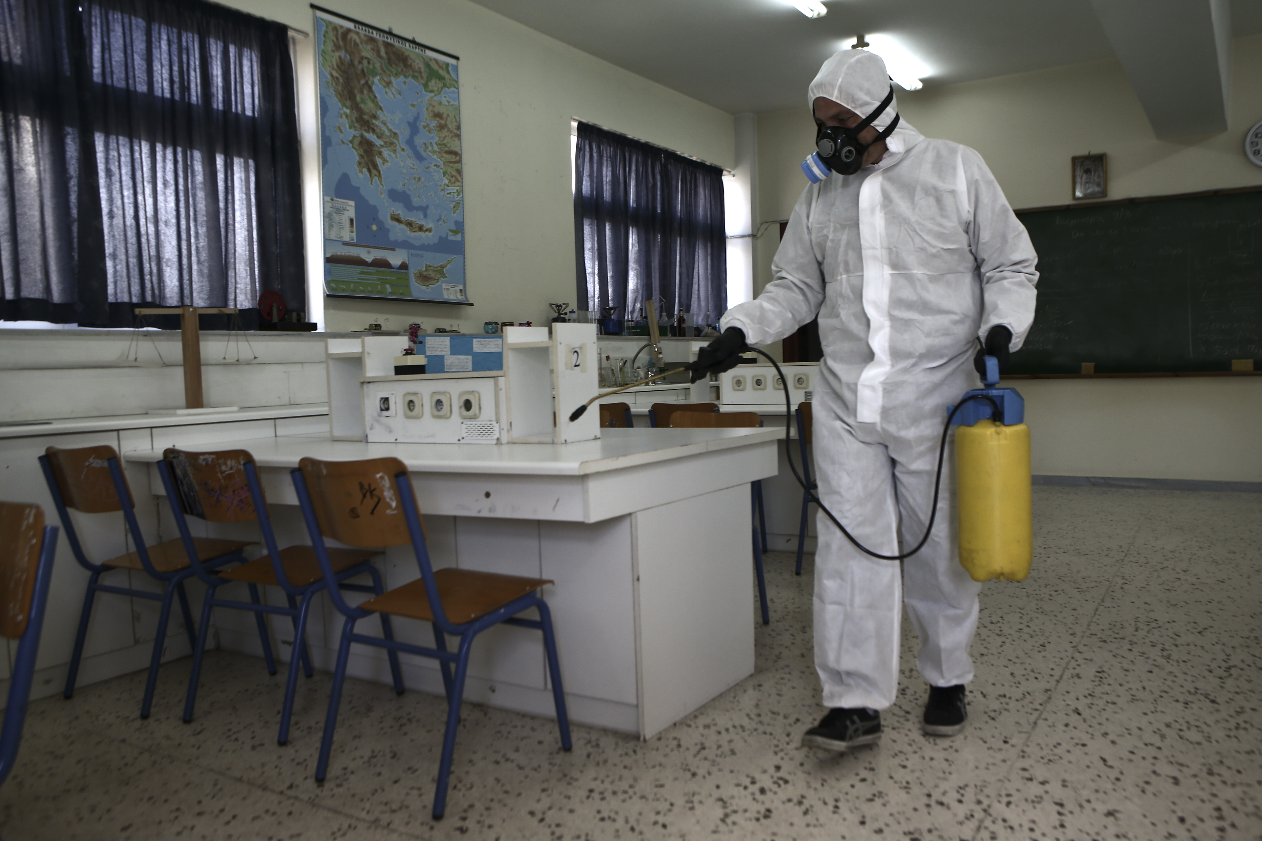 A worker wearing a protective suit sprays disinfectant inside a classroom at a high school in Athens, Greece on Friday, March 6.