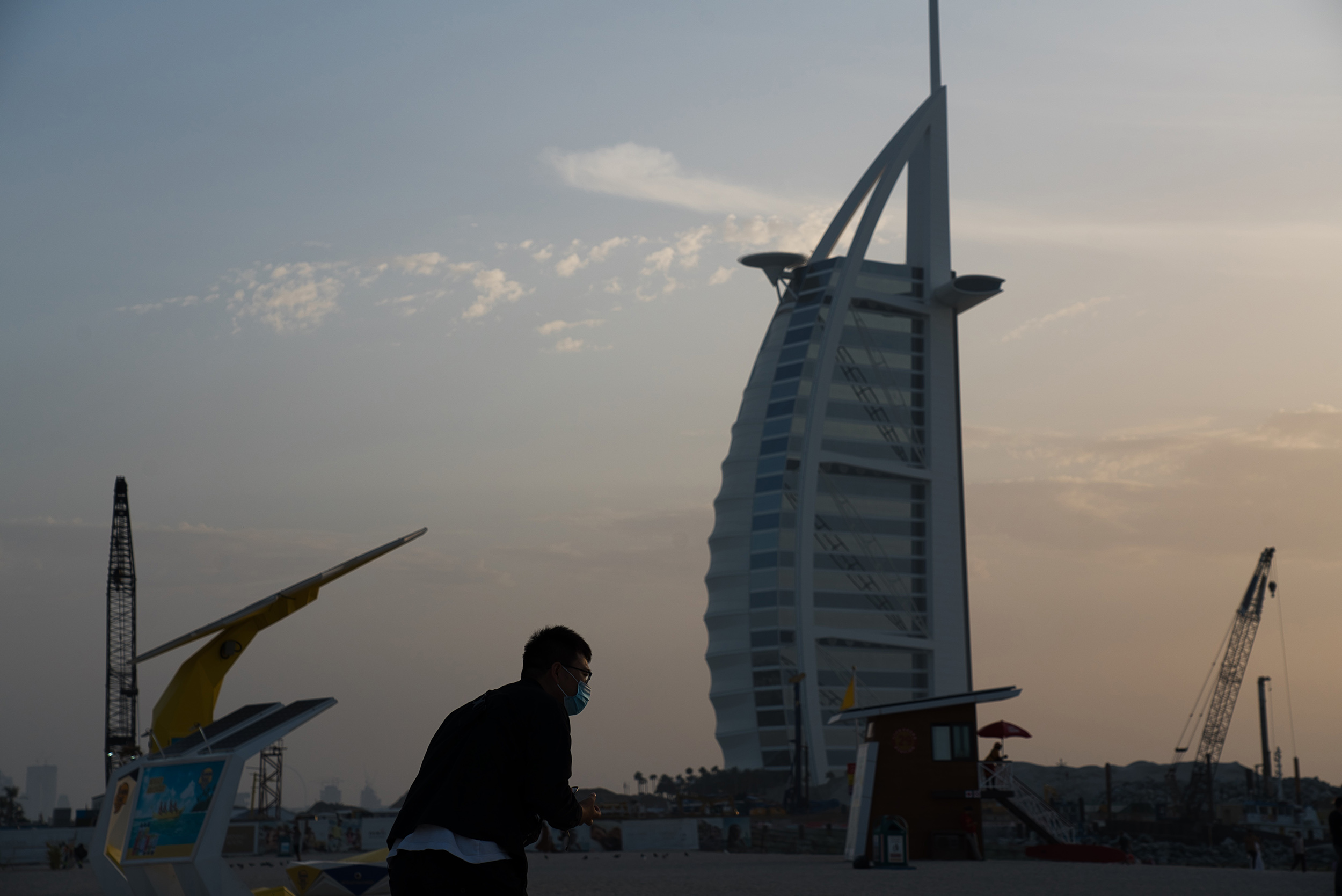 A tourist wearing a mask takes a picture in front of the sail-shaped Burj Al Arab luxury hotel in Dubai, United Arab Emirates, on Friday, March 20, 2020.
