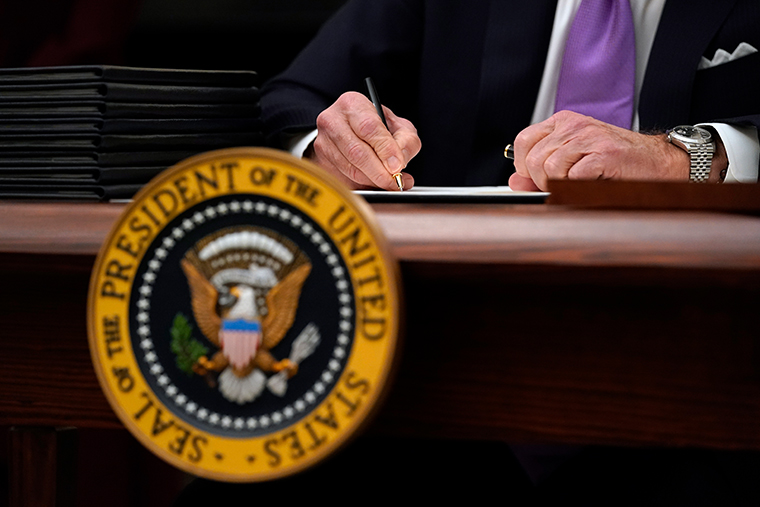 President Joe Biden signs executive orders after speaking about the coronavirus in the State Dinning Room of the White House, Thursday, Jan. 21, 2021, in Washington.