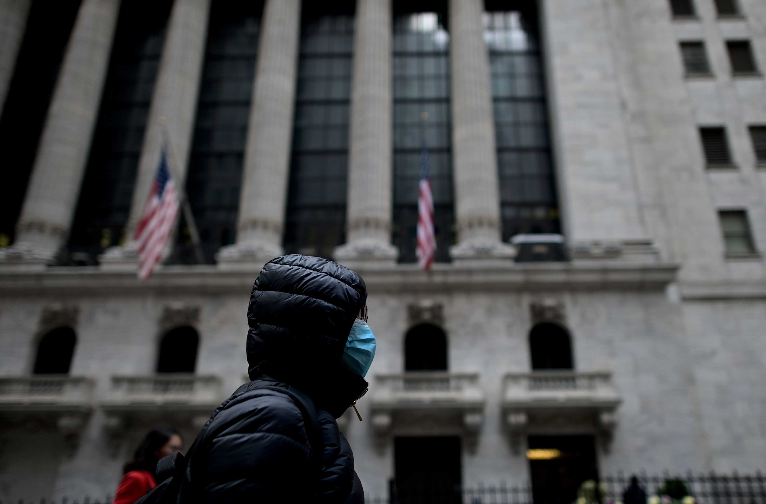A person wearing a facial mask passes the New York Stock Exchange on February 3.