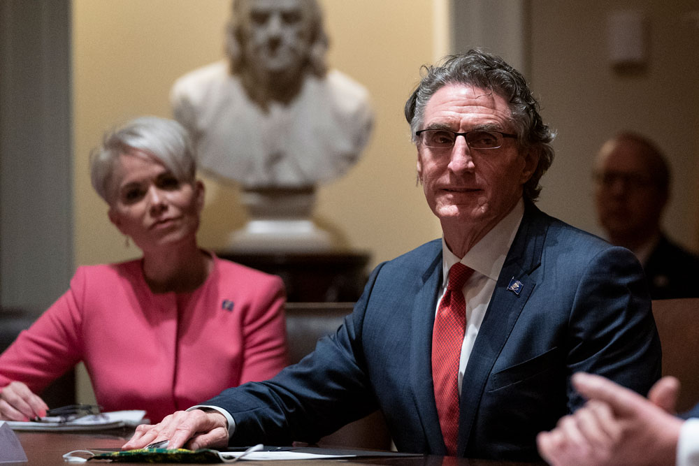 Michelle Kommer, commissioner of the North Dakota Department of Commerce, left, and North Dakota Gov. Doug Burgum, center, listen as President Donald Trump speaks during a meeting about the coronavirus response at the White House on Wednesday, May 13, in Washington.