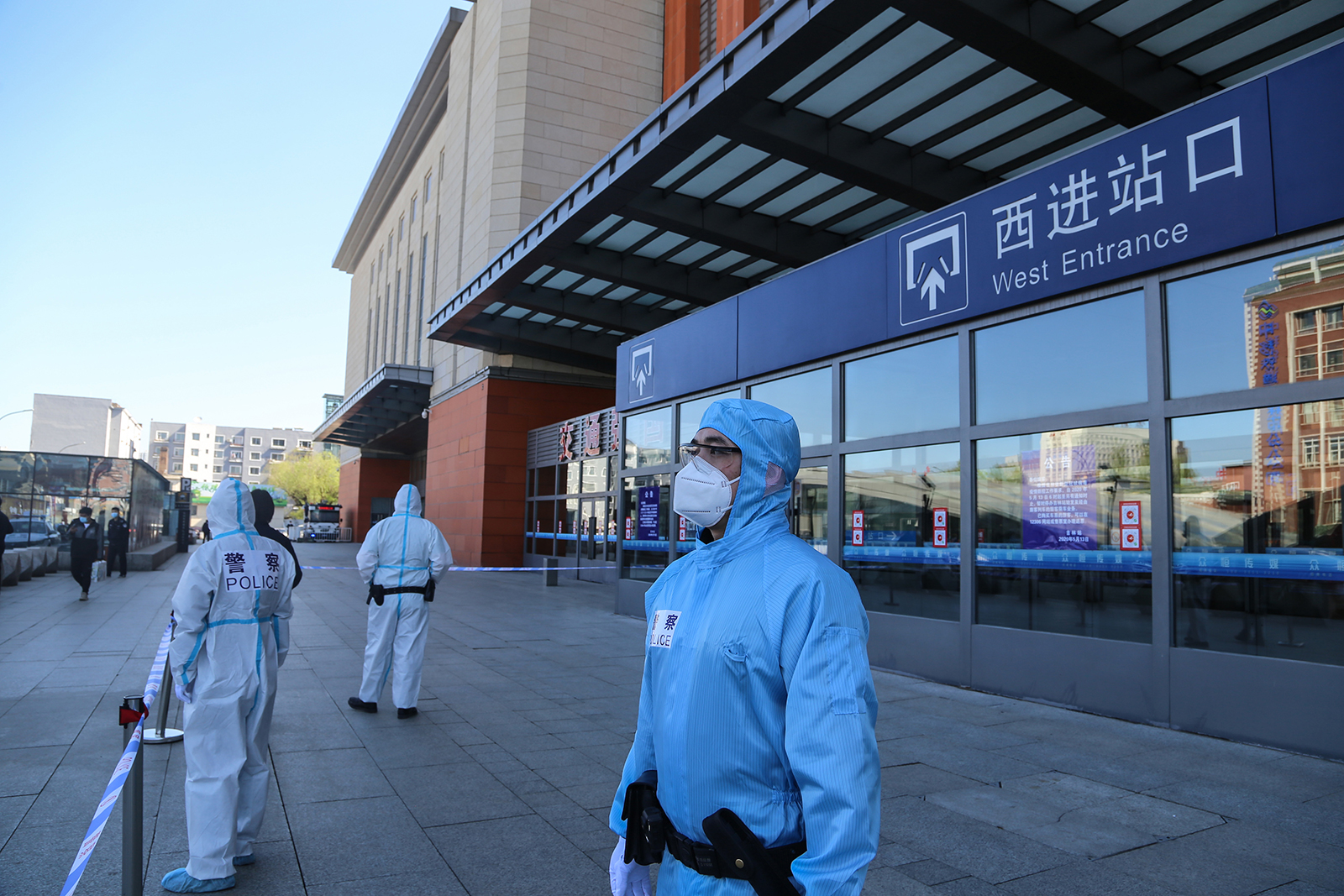 Police officers clad in protective suits stand guard outside Jilin city's railway station in Jilin province on May 13.