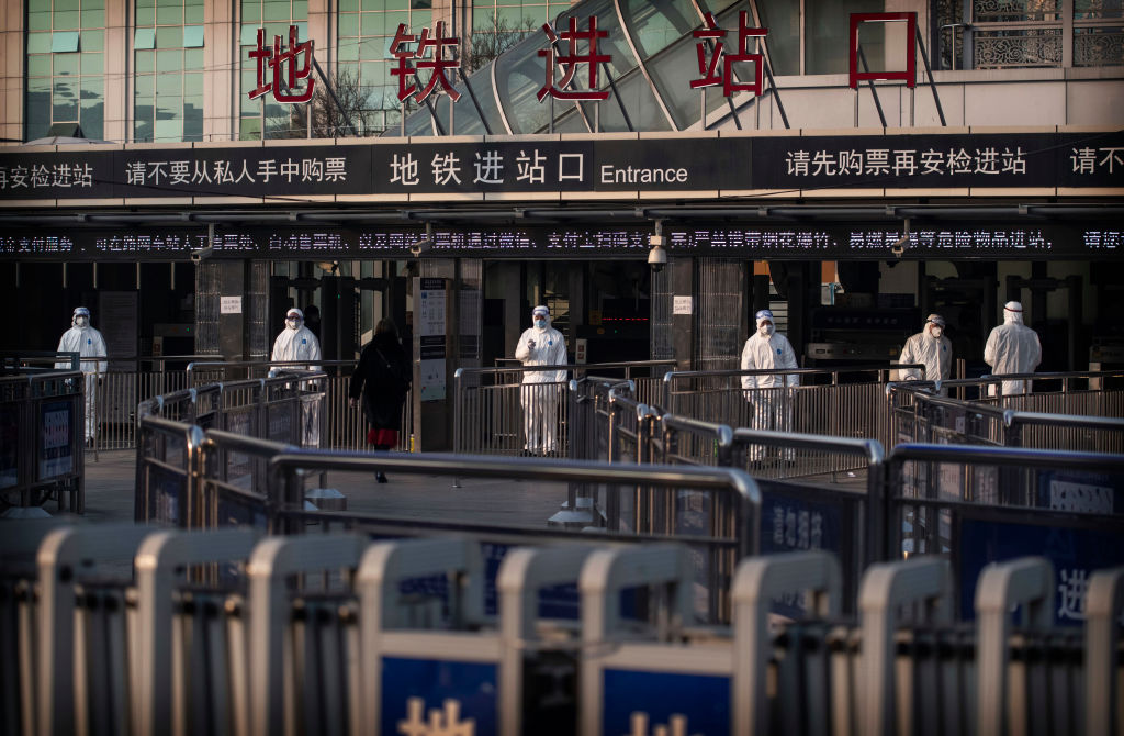 Chinese health workers wait to check the temperatures of travellers entering a subway station on January 25, 2020 in Beijing, China.