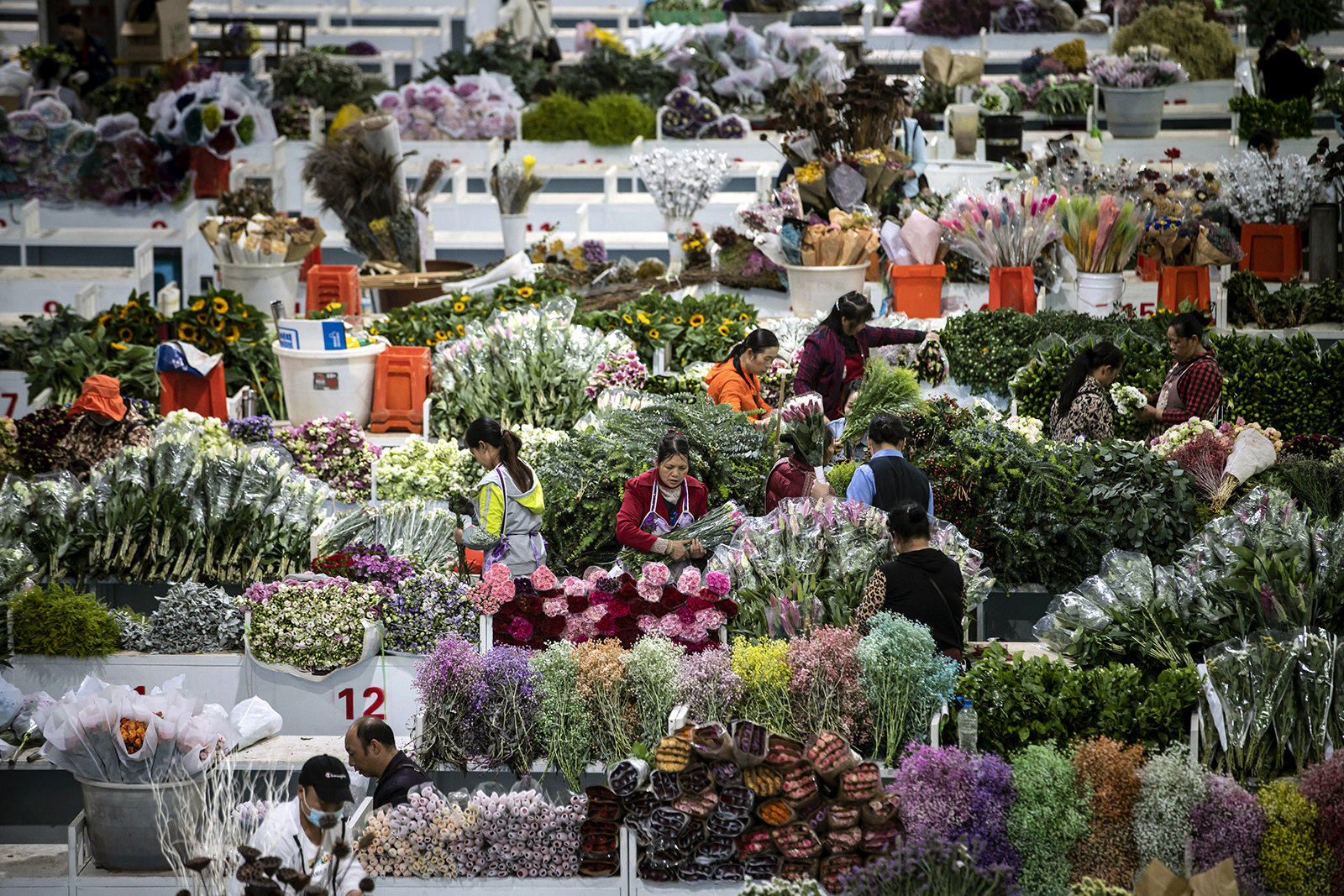 Vendors prepare for the start of the morning retail shift at the Dounan Flower Market in Kunming, Yunnan Province, China, on July 14.