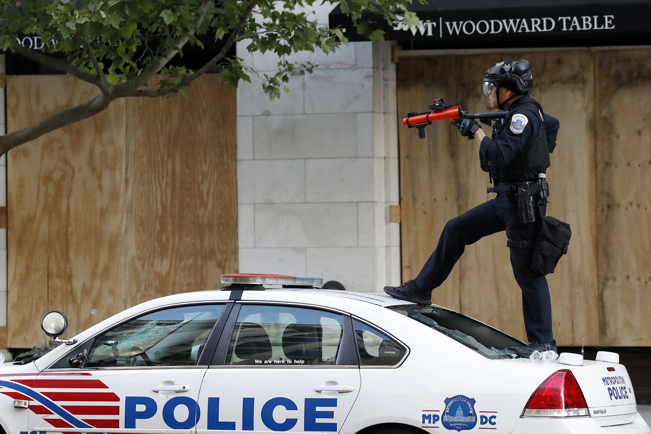 A Metropolitan Police Department officer stands on a vandalized police cruiser as demonstrators protest the death of George Floyd in Washington DC, on Sunday, May 31.