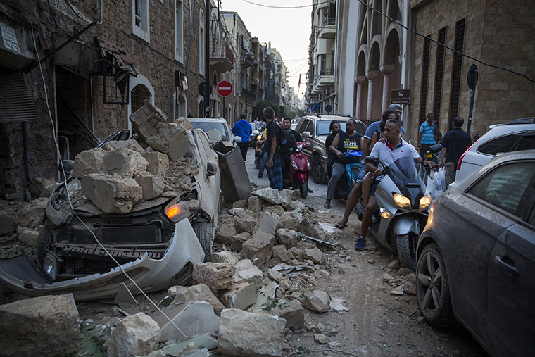 People ride past a car destroyed after a building wall collapsed on August 4.