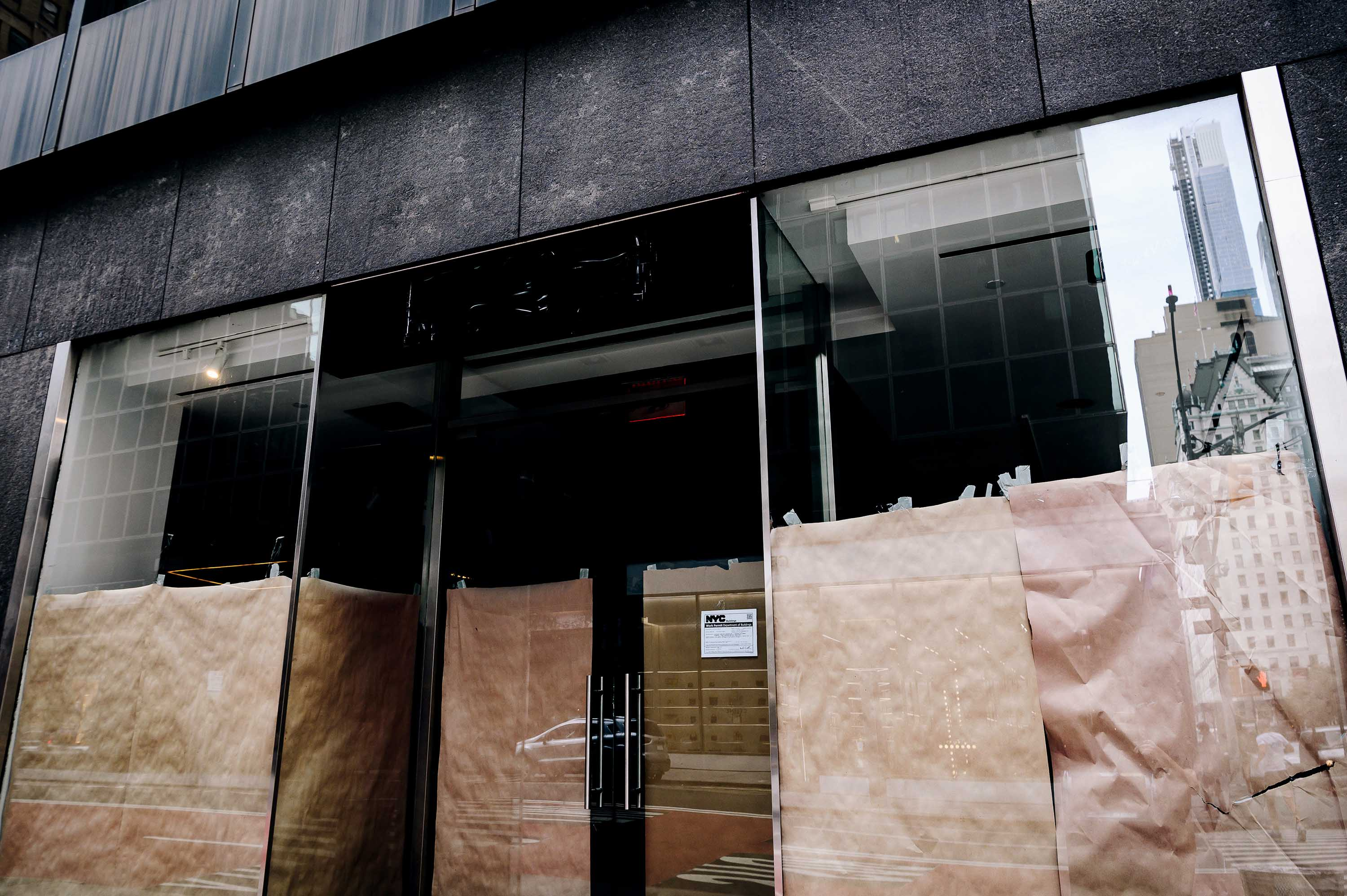Paper covers the windows of a closed storefront on Madison Avenue in New York, on September 26.