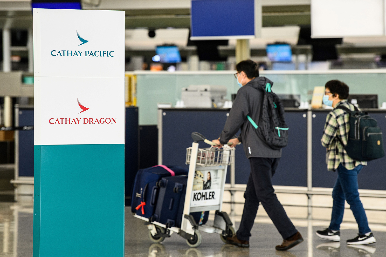 Passengers walk past signage for Cathay Pacific and Cathay Dragon near the city's flagship carrier check-in counters at Hong Kong International Airport, on October 20.