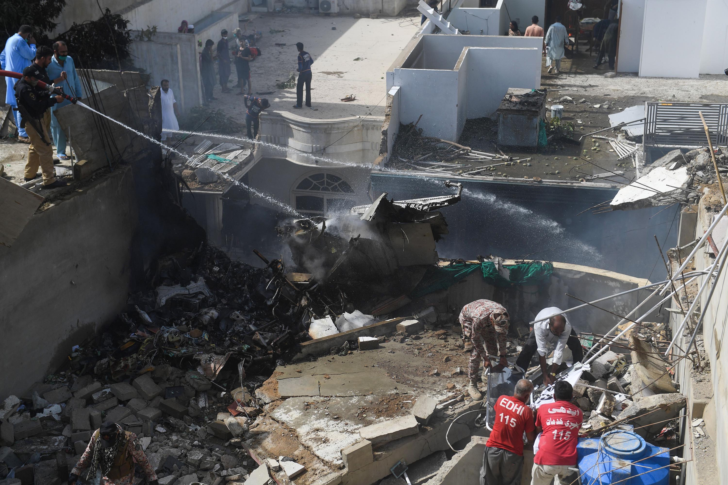 Emergency personnel work at the scene of the Pakistan International Airlines crash in Karachi on Friday.