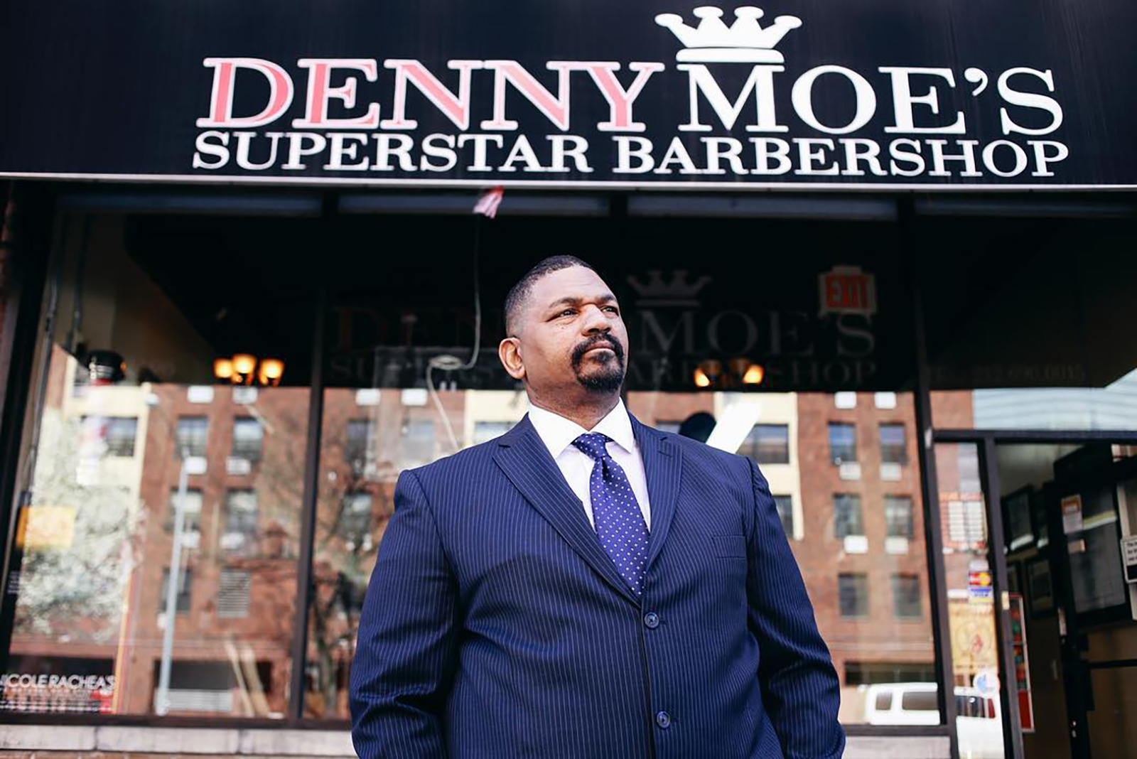"Dennis ""Denny Moe"" Mitchell, 54, stands outside of Denny Moe's Superstar Barbershop in Harlem, New York in an undated photo."