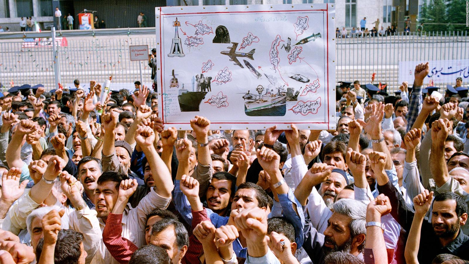 "Thousands of Iranians chanting ""Death to America,"" participate in a mass funeral for 76 people killed when the USS Vincennes shot down Iran Air Flight 655, in Tehran, Iran, July 7, 1988. They hold aloft a drawing depicting the incident."