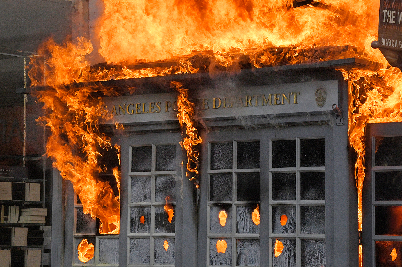 A Los Angeles Police Department kiosk burns in The Grove shopping center during a protest over the death of George Floyd on Saturday, May 30.