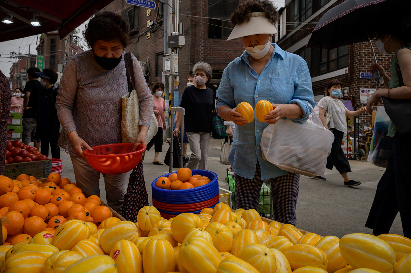 Shoppers walk through a market in Seoul on June 10.