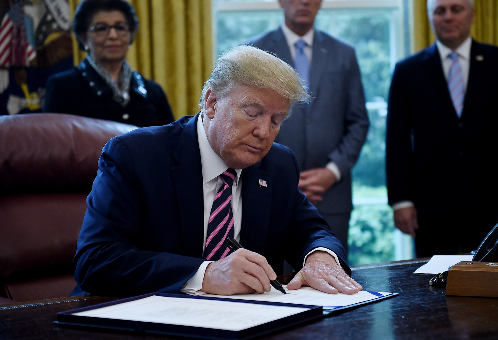 US President Donald Trump signs the Paycheck Protection Program and Health Care Enhancement Act in the Oval Office of the White House in Washington, DC, on April 24.