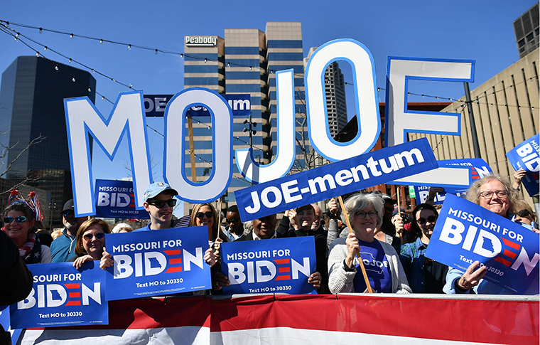 Supporters hold up signs before a rally at Kiener Plaza Park in St. Louis, Missouri on Saturday, March 7.
