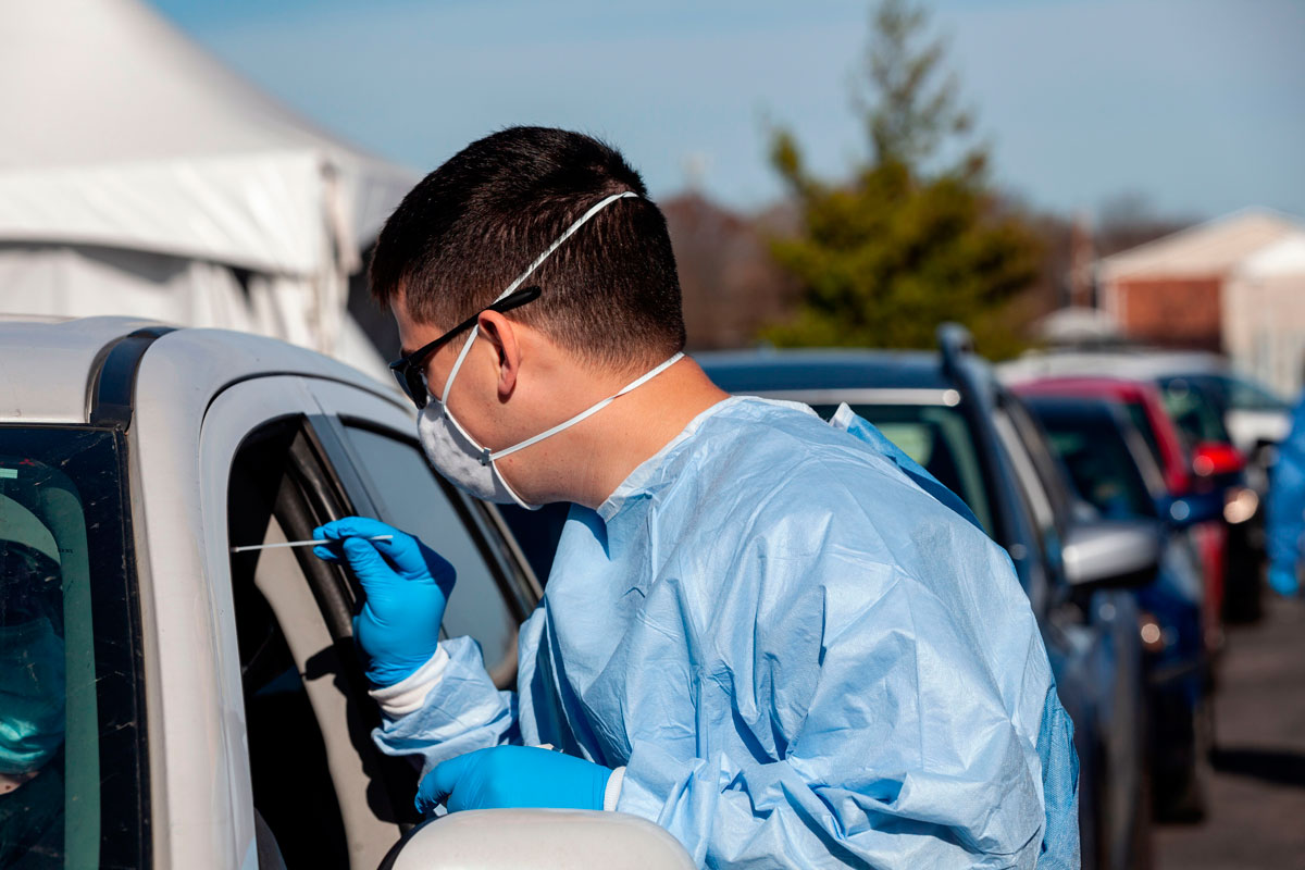 A healthcare worker administers a free Covid-19 test to a person in a car at the Columbus West Family Health and Wellness Center in Columbus, Ohio on November 19.