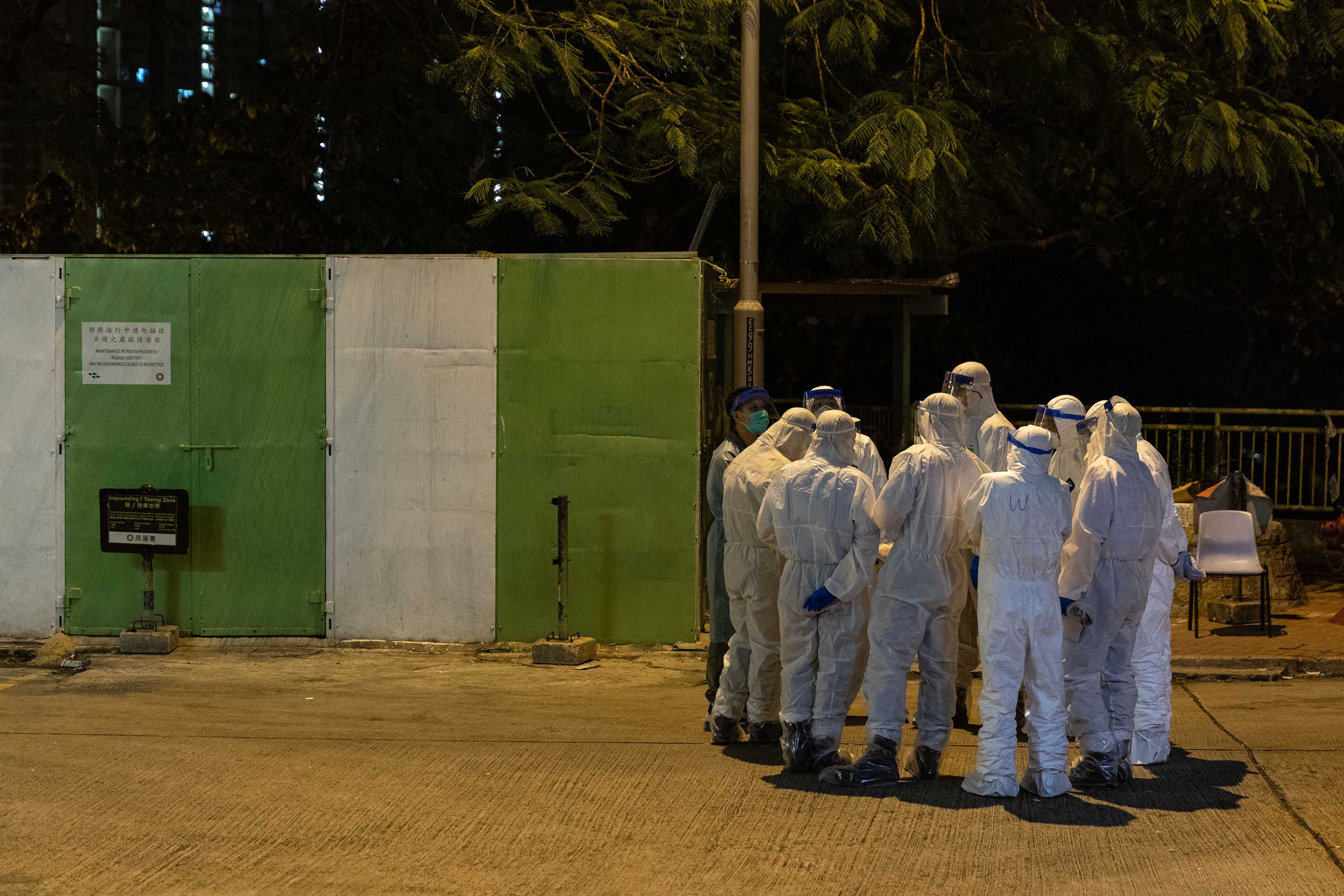 Health workers gather outside Hong Mei House in Hong Kong on Monday, after coronavirus cases were confirmed at the residential complex.