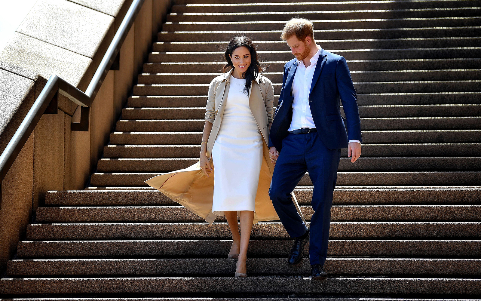 Britain's Prince Harry and his wife Meghan walk down the stairs of the iconic Opera House to meet people on October 16, 2018.