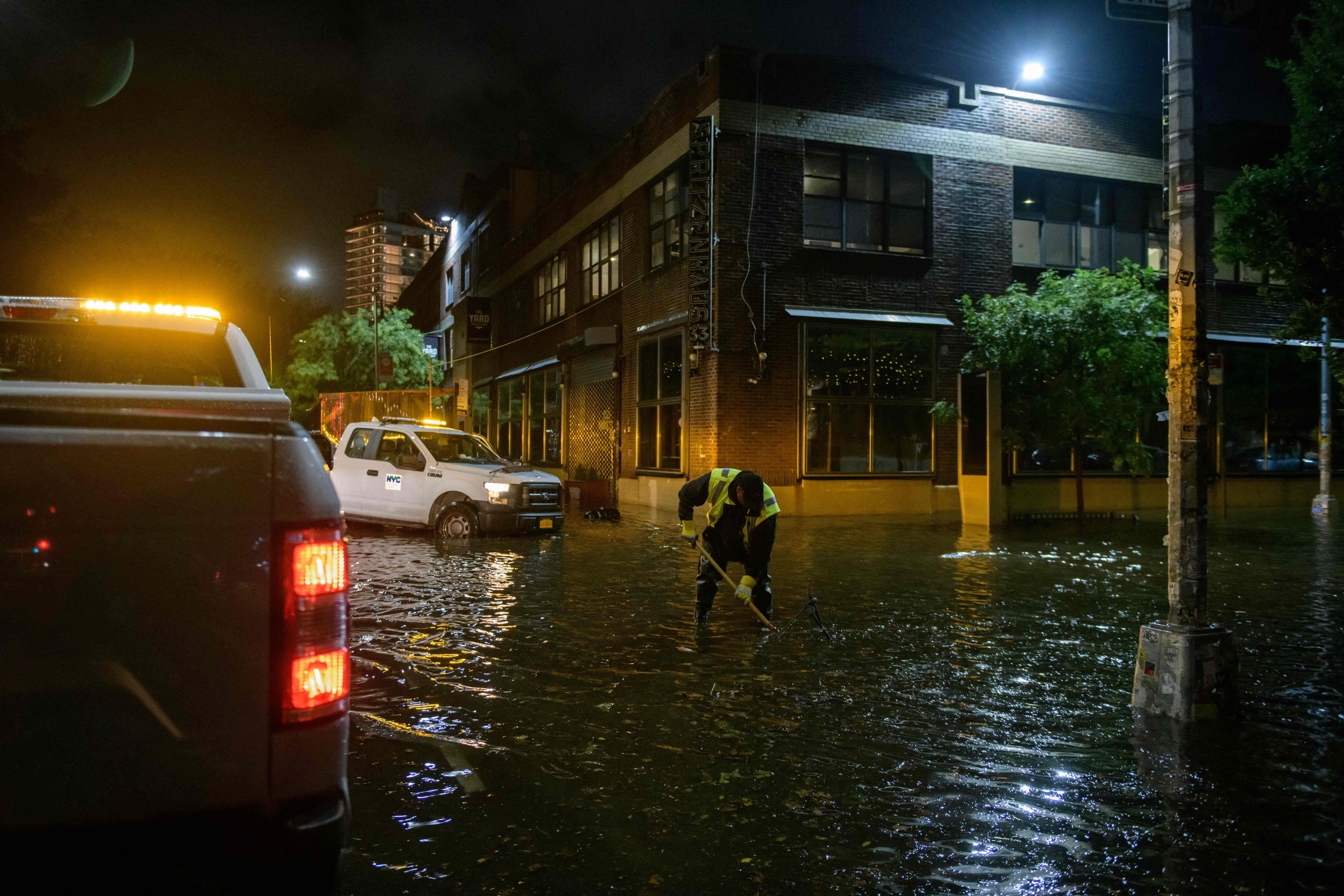 A worker unblocks drains on a street affected by floodwaters in Brooklyn, New York, on September 2.