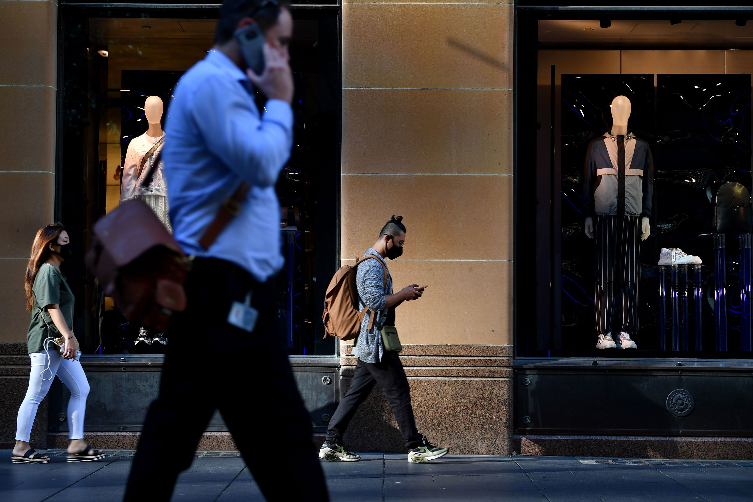 People walk past a retail store in Sydney on March 19.