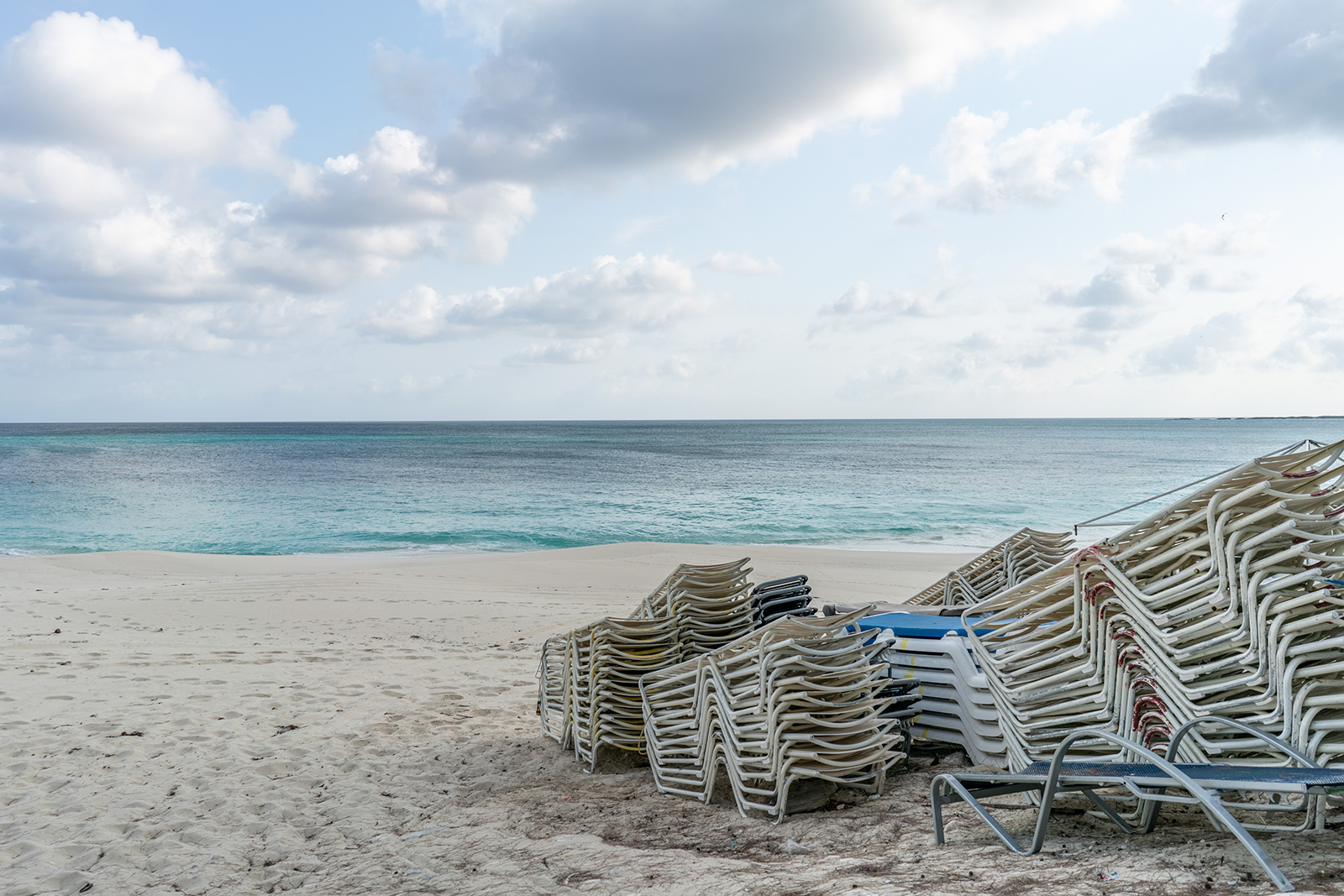 Lounge chairs sit stacked on a beach while temporarily closed in Nassau, Bahamas, on Friday, April 24.